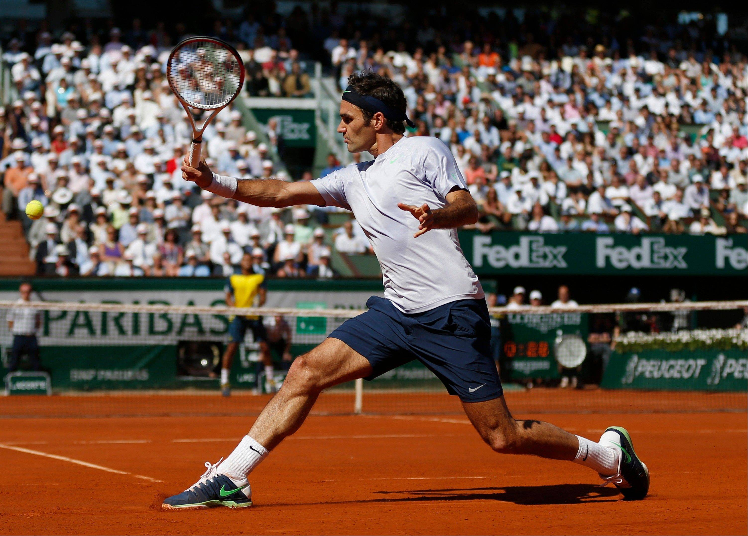 Switzerland's Roger Federer returns the ball to France's Jo-Wilfried Tsonga during their quarterfinal match of the French Open tennis tournament at the Roland Garros stadium Tuesday, June 4, 2013 in Paris.