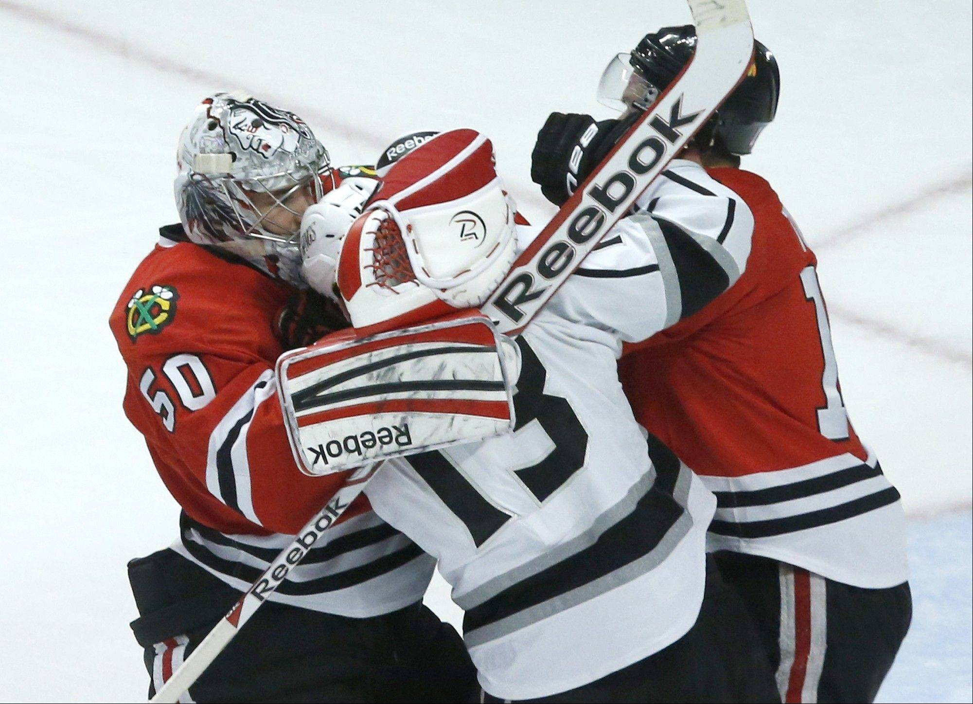 Blackhawks goalie Corey Crawford pulls on the head of Kings left wing Kyle Clifford and separates him from the Hawks' Jonathan Toews during the third period in Game 2 of the Western Conference finals Sunday at the United Center.