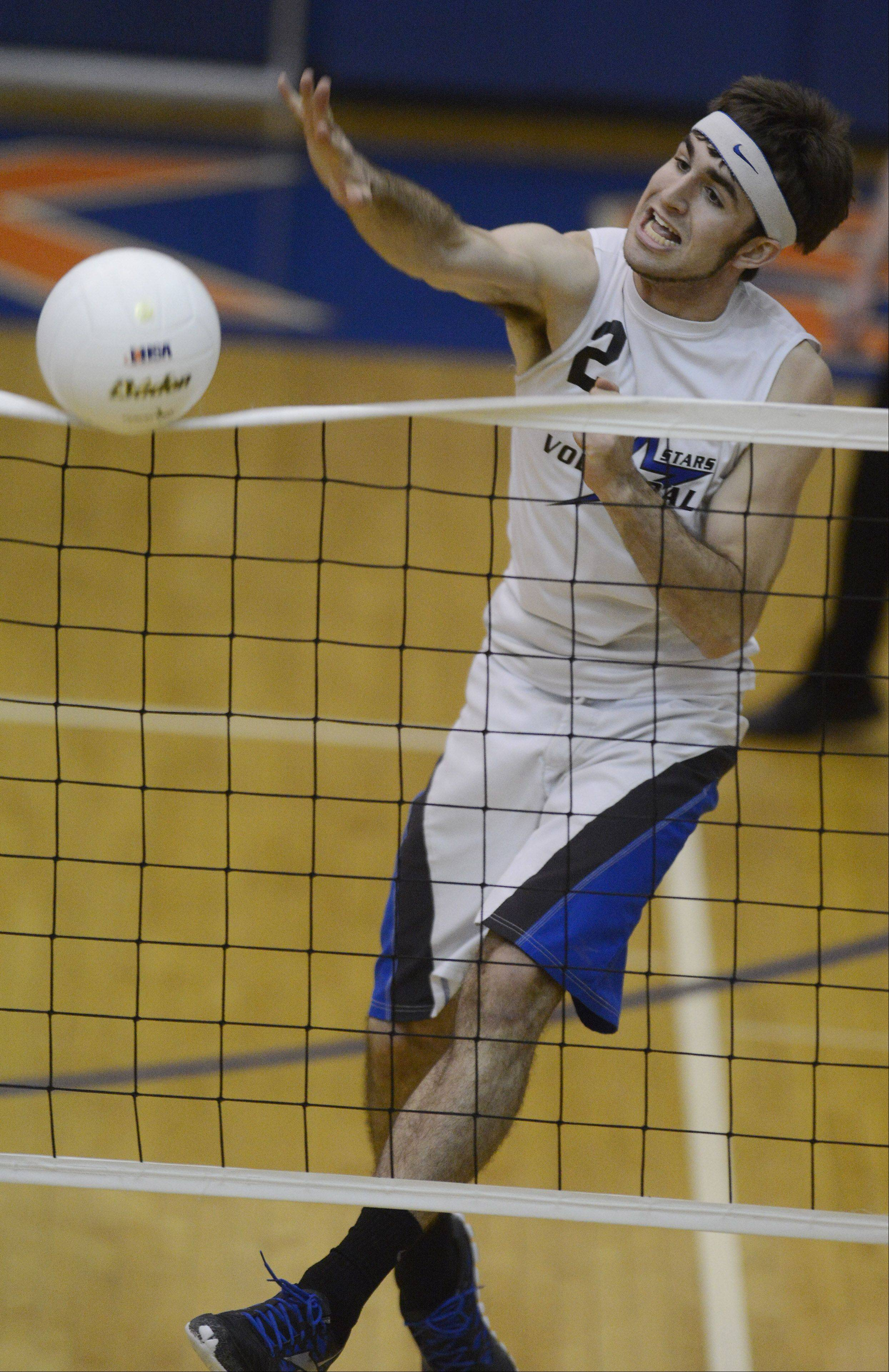 St. Charles North's Jonathan Orech gets a kill during Saturday's volleyball match against Glenbrook South at Hoffman Estates High School.