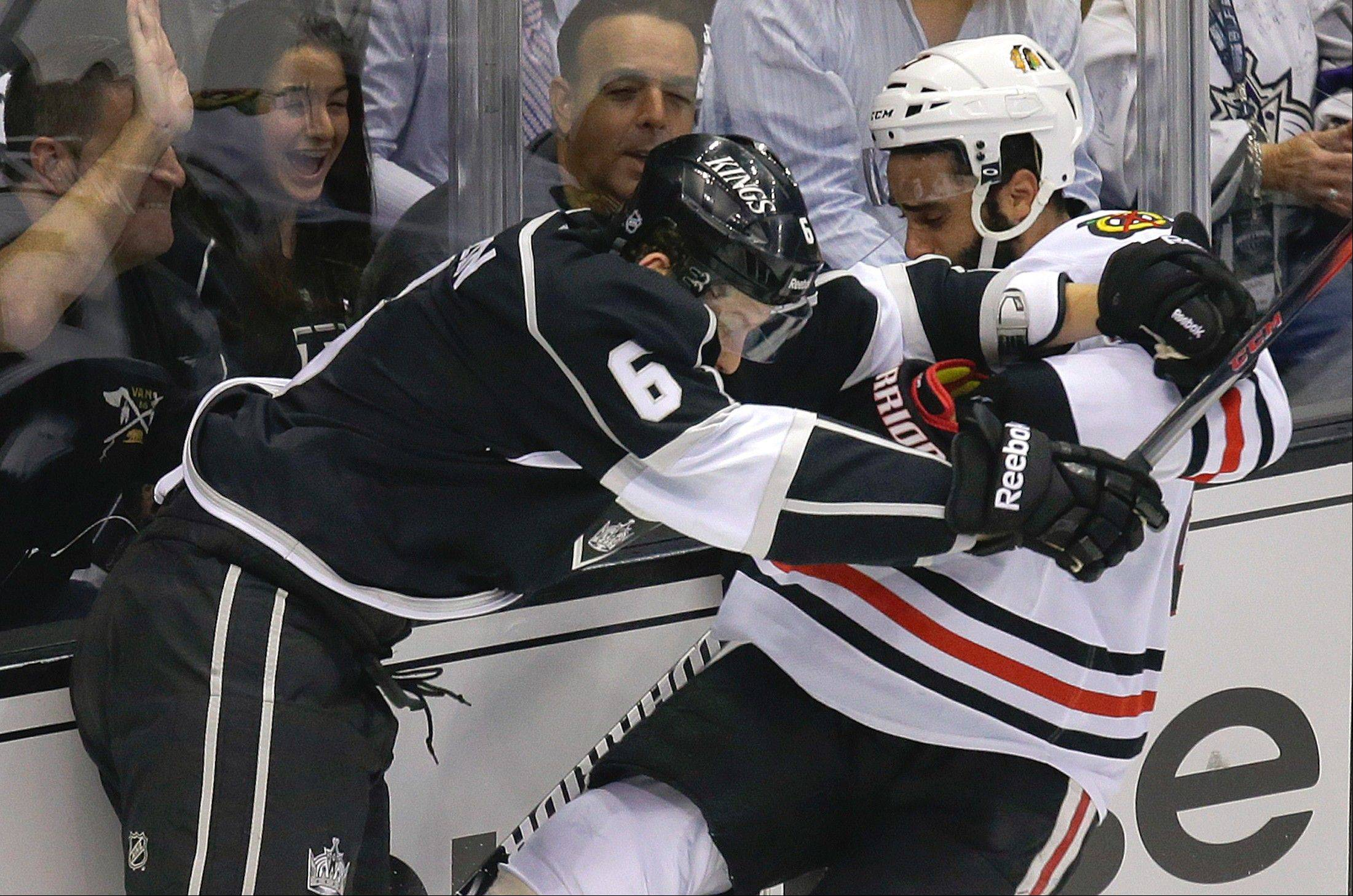 Los Angeles Kings defenseman Jake Muzzin shoves Blackhawks defenseman Johnny Oduya during the first period of Game 3 on Tuesday night. The Kings won 3-1.