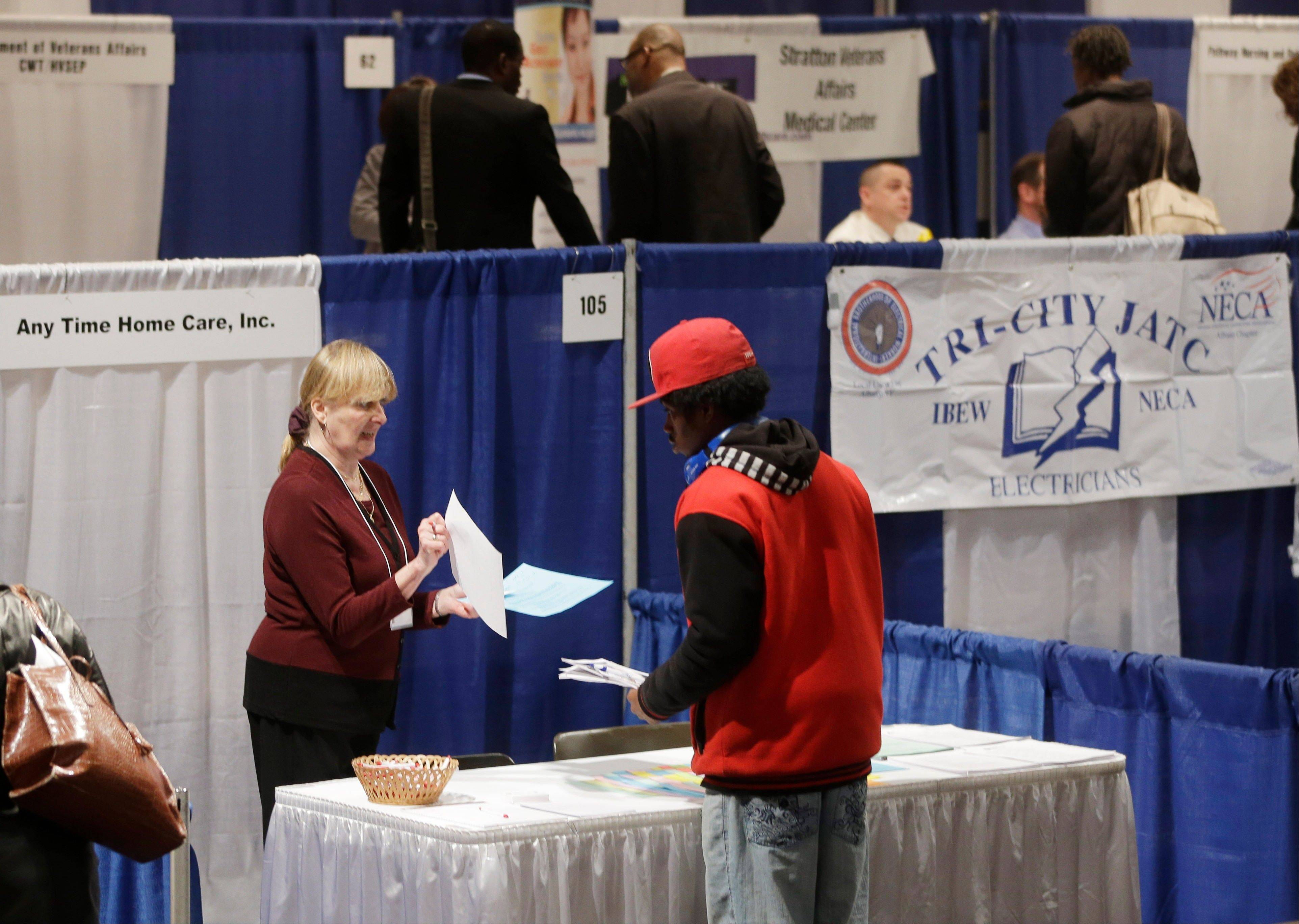 Kathie Maiello of Any-Time Home Care, left, talks with Jashod Chaney, of Albany, at the Dr. King Career Fair at the Empire State Plaza Convention Center, in Albany, N.Y. Payroll processor ADP said Wednesday, June 5, 2013, that companies added 135,000 jobs in May.