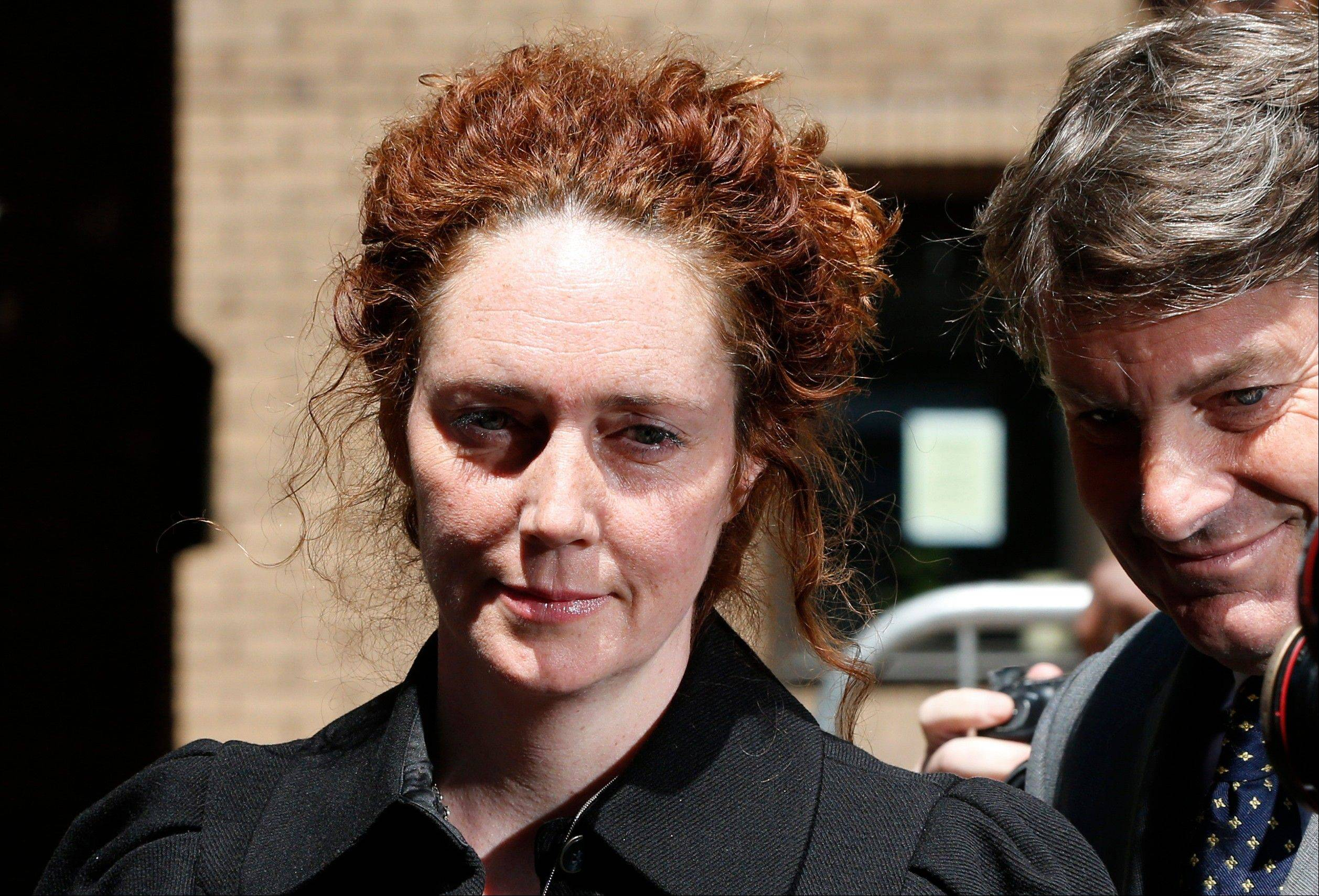 Former News International chief executive Rebekah Brooks, accompanied by her husband Charlie, right, leaves a court after entering a not guilty plea to charges related to phone hacking, in London, Wednesday, June 5, 2013. Brooks on Wednesday denied charges of phone hacking, bribing public officials and trying to thwart a police investigation into tabloid wrongdoing.