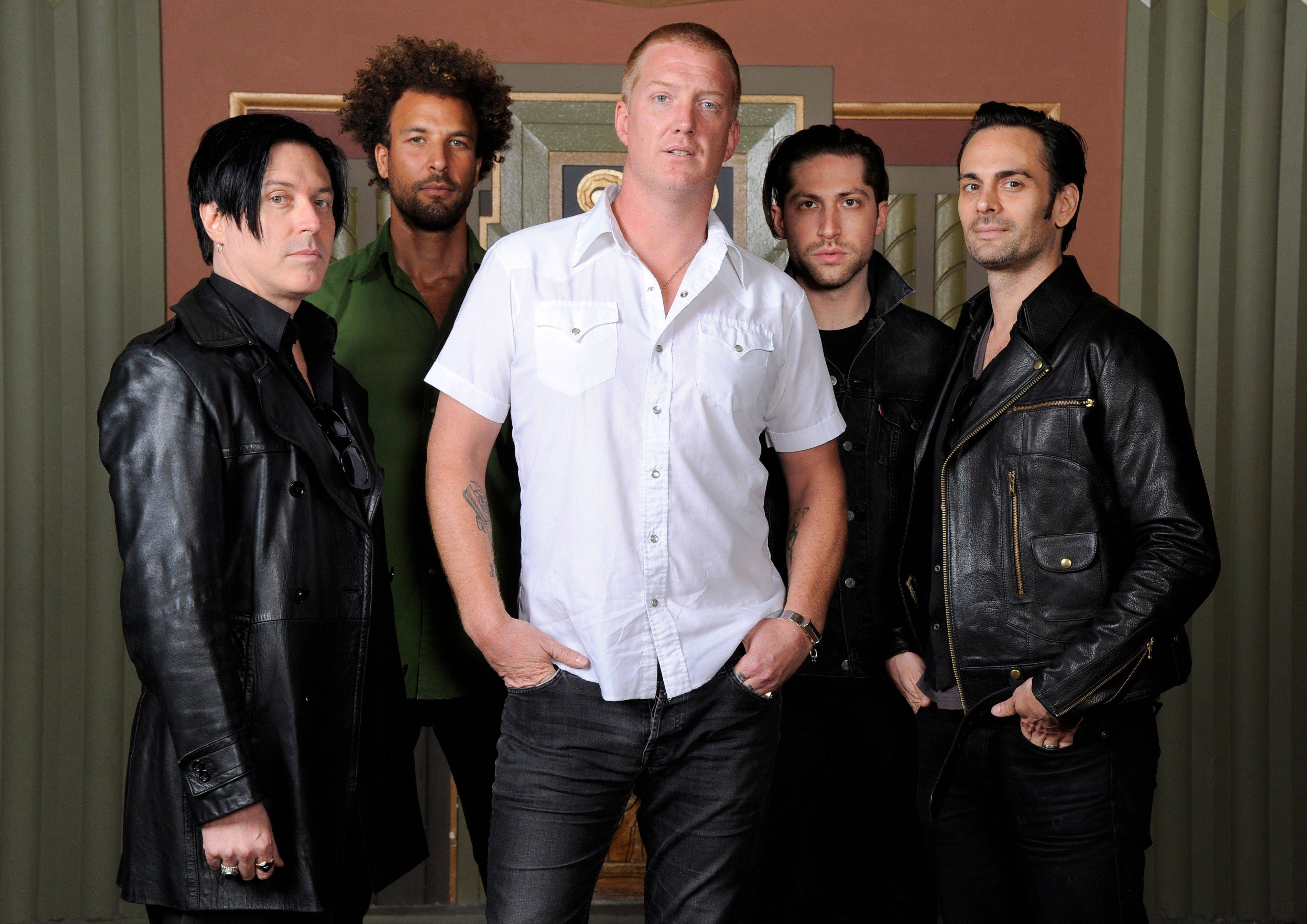 "Queens of the Stone Age — Troy Van Leeuwen, left, Jon Theodore, Josh Homme, Michael Shuman and Dean Fertita — released their first album in six years, ""... Like Clockwork,"" on Tuesday. They're heading to Chicago to play Lollapalooza on Friday, Aug. 2."