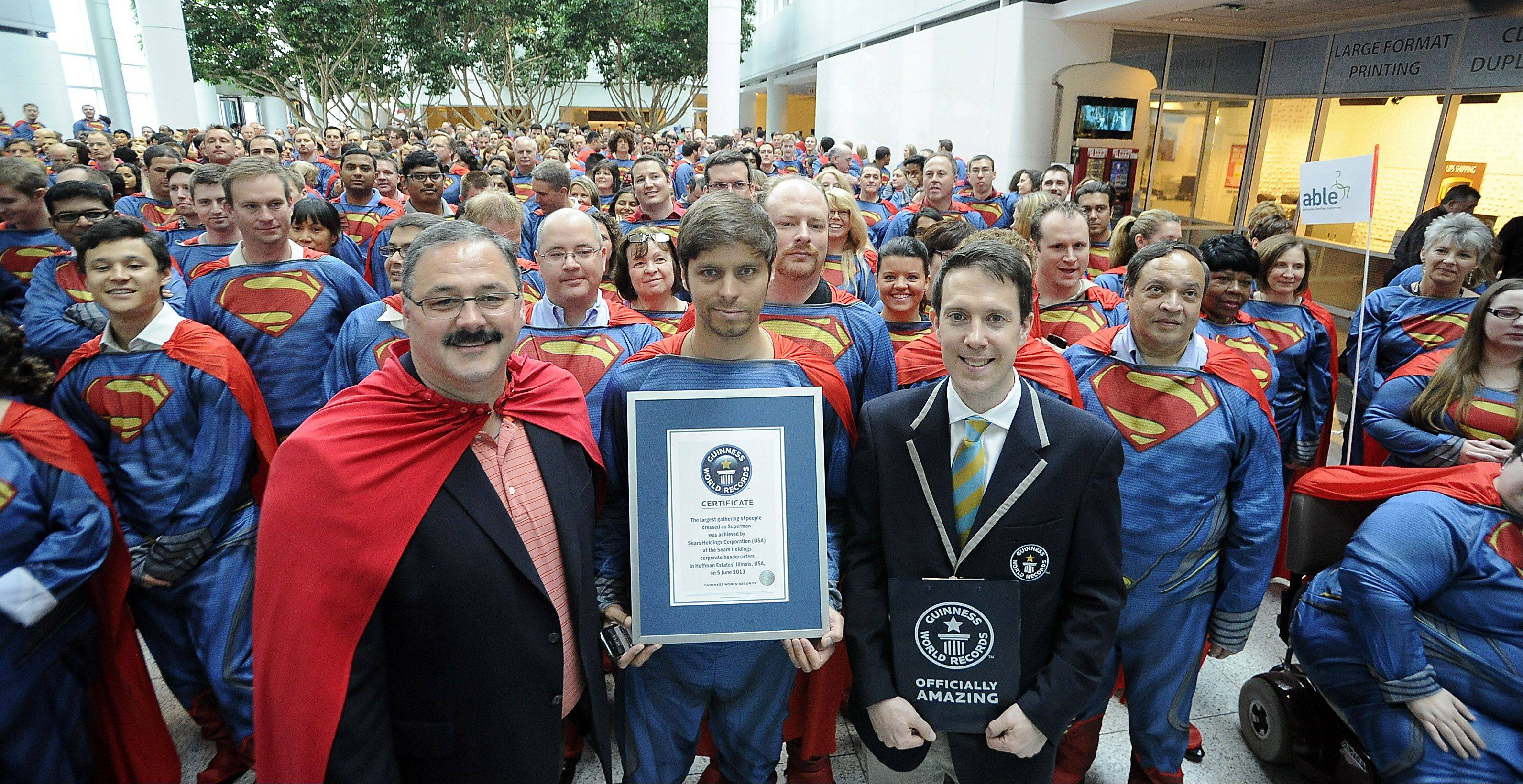 From left, Ron Boire, executive vice president of Sears Holdings Corp., Sears employee Vitaly Demin and Philip Robertson, adjudicator with Guinness World Records, show off the certificate.