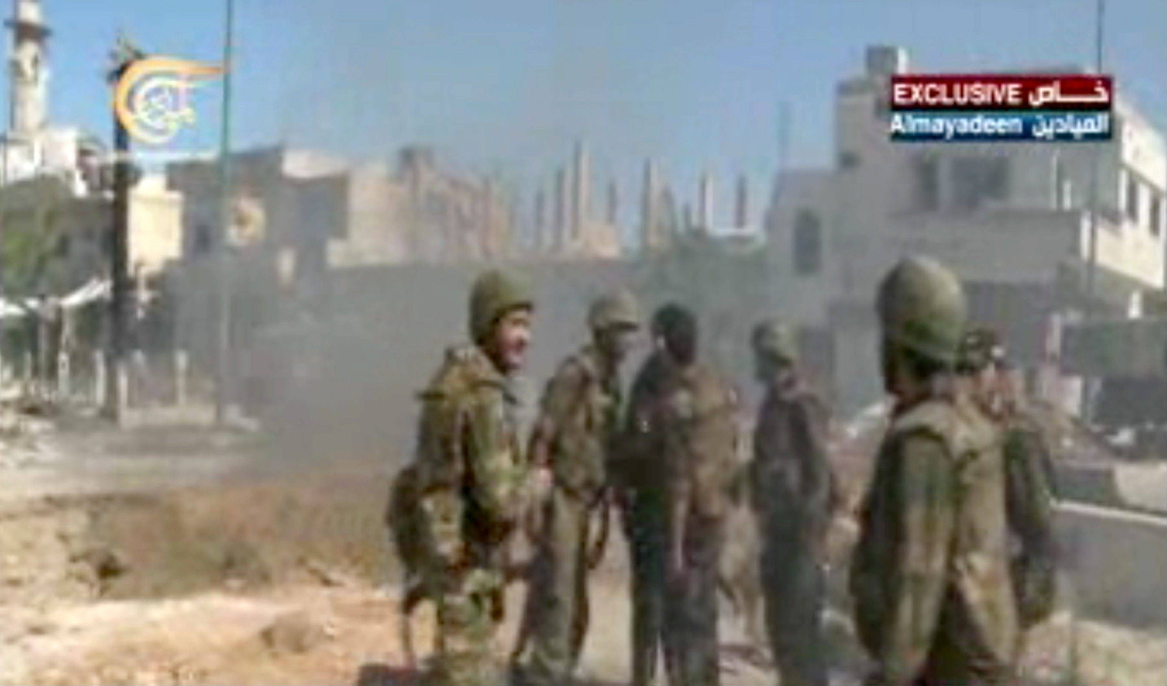 This image made from video broadcast Wednesday on Al-Mayadeen Television shows Syrian army troops in Qusair, Syria. The Syrian army triumphantly announced Wednesday the capture of a strategic town near the Lebanese border, telling the nation it has �cleansed� the rebel-held Qusair of �terrorists� fighting President Bashar Assad�s troops. The capture of the town, which lies close to the Lebanese border, solidifies some of the regime�s recent gains on the ground that have shifted the balance of power in Assad�s favor in the Syrian civil war.