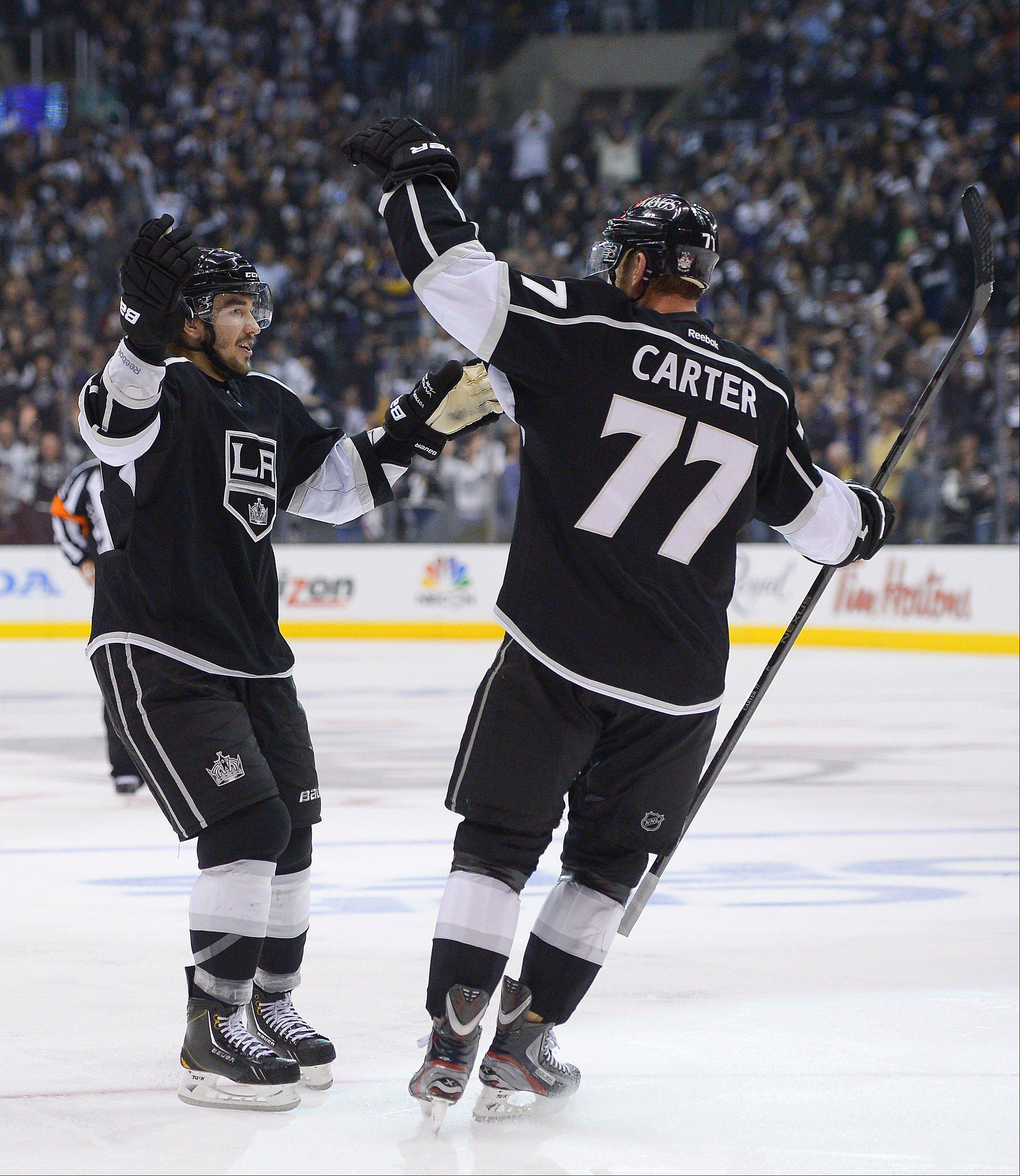 Los Angeles Kings defenseman Slava Voynov, left, celebrates with center Jeff Carter (77) after scoring a goal against the Chicago Blackhawks during the second period in Game 3 of the NHL hockey Stanley Cup playoffs Western Conference finals, Tuesday, June 4, 2013, in Los Angeles. (AP Photo/Mark J. Terrill)