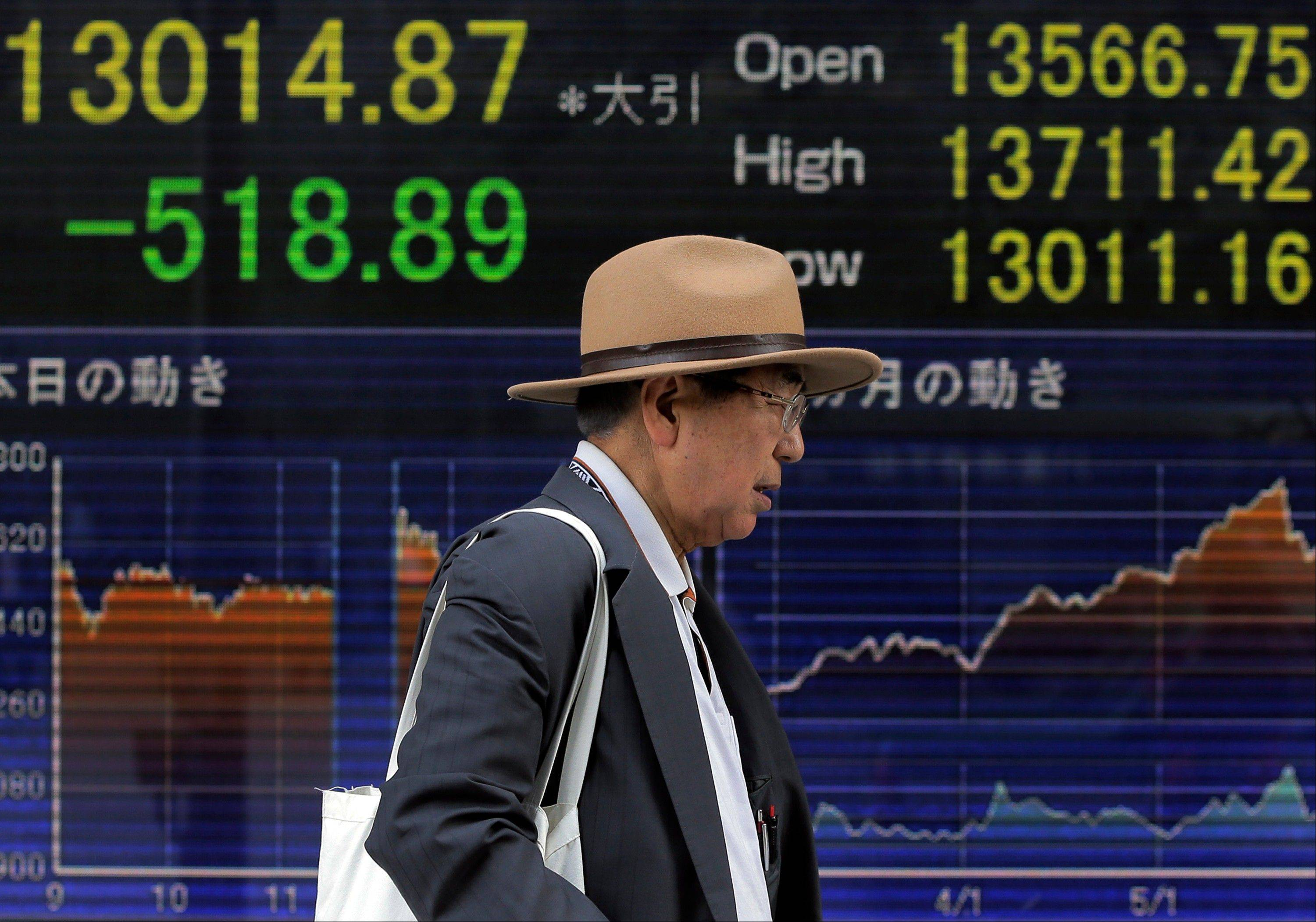 A man walks by an electronic stock board of a securities firm Wednesday in Tokyo. Asian stock markets fell Wednesday as signs the U.S. Federal Reserve might scale back its super-loose monetary policy caused investors to trim equity investments.