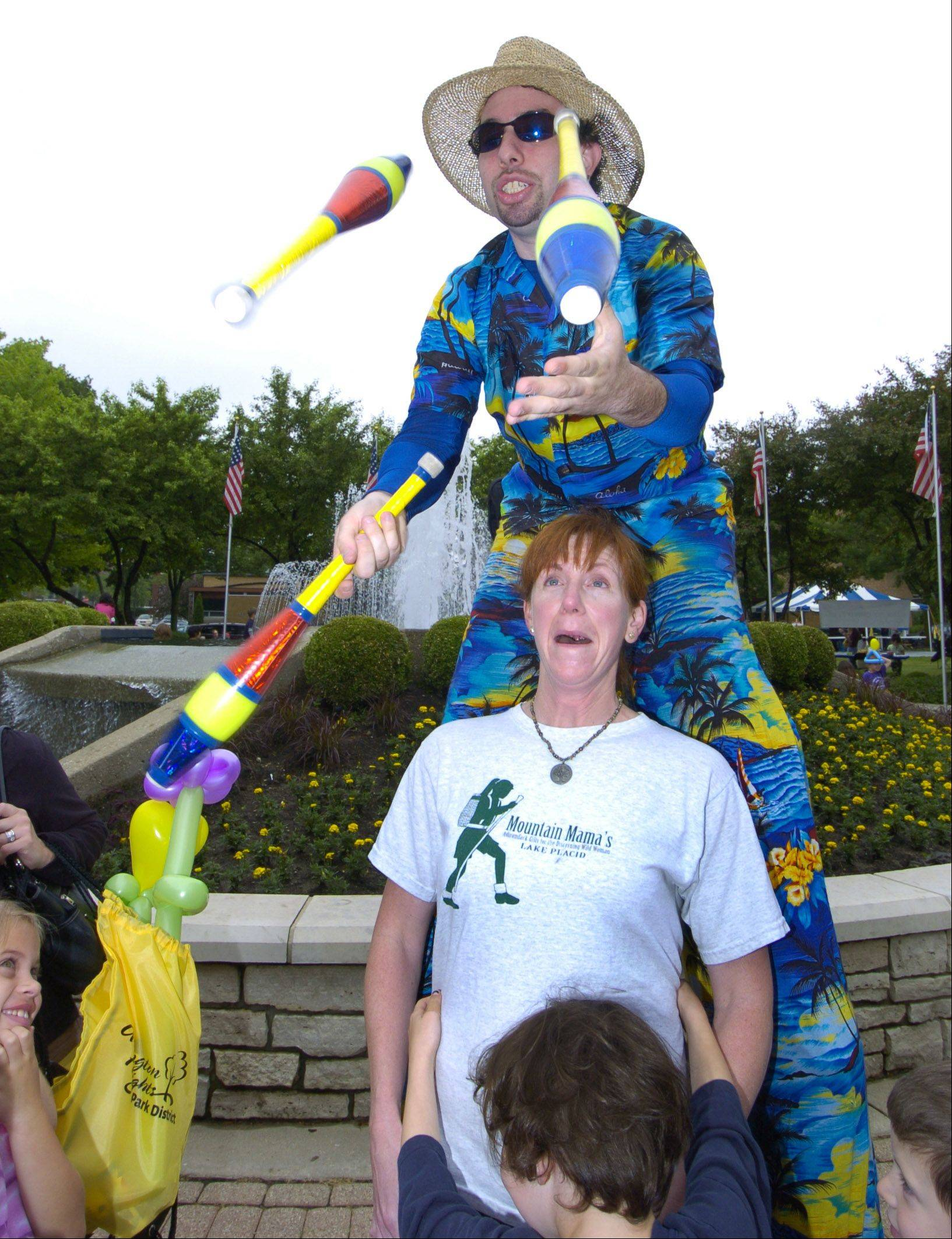 Stilt-walker Jason Kollum juggles just above Arlington Heights resident Gretchen Benne's head during a previous Picnic in the Park in Arlington Heights.