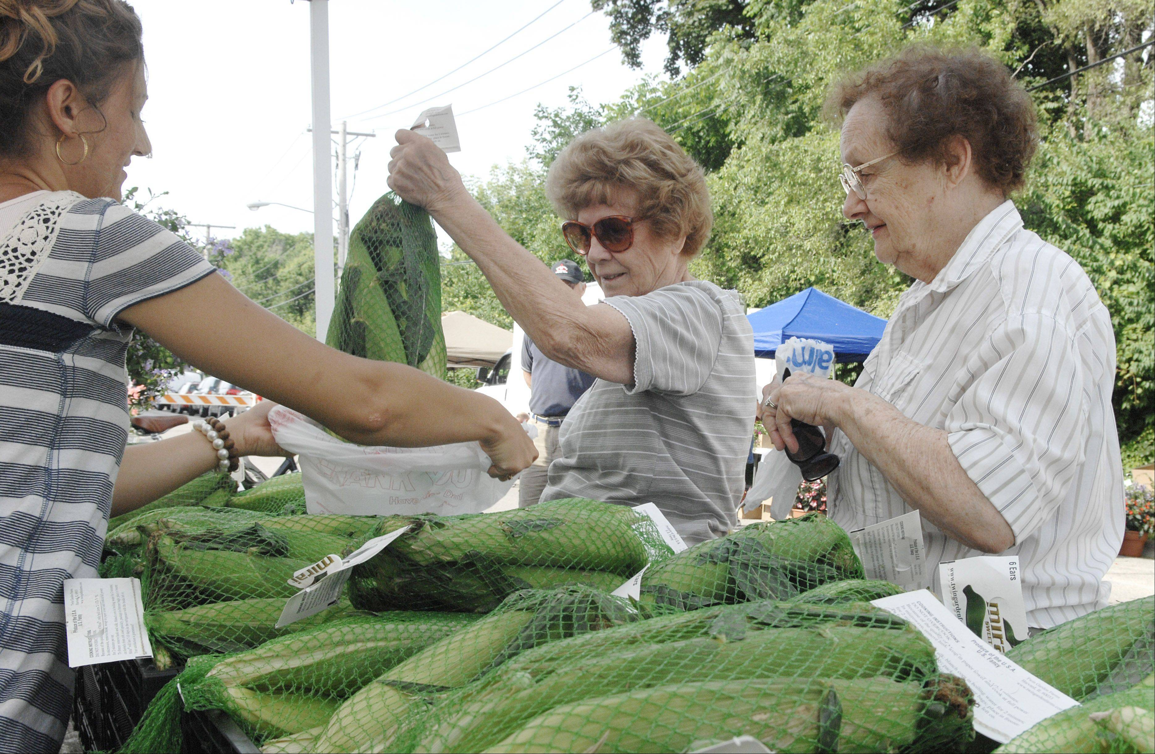 Shoppers purchase Mirai sweet corn at the Batavia Farmers Market. The market, which starts Saturday, is moving to North River Street.