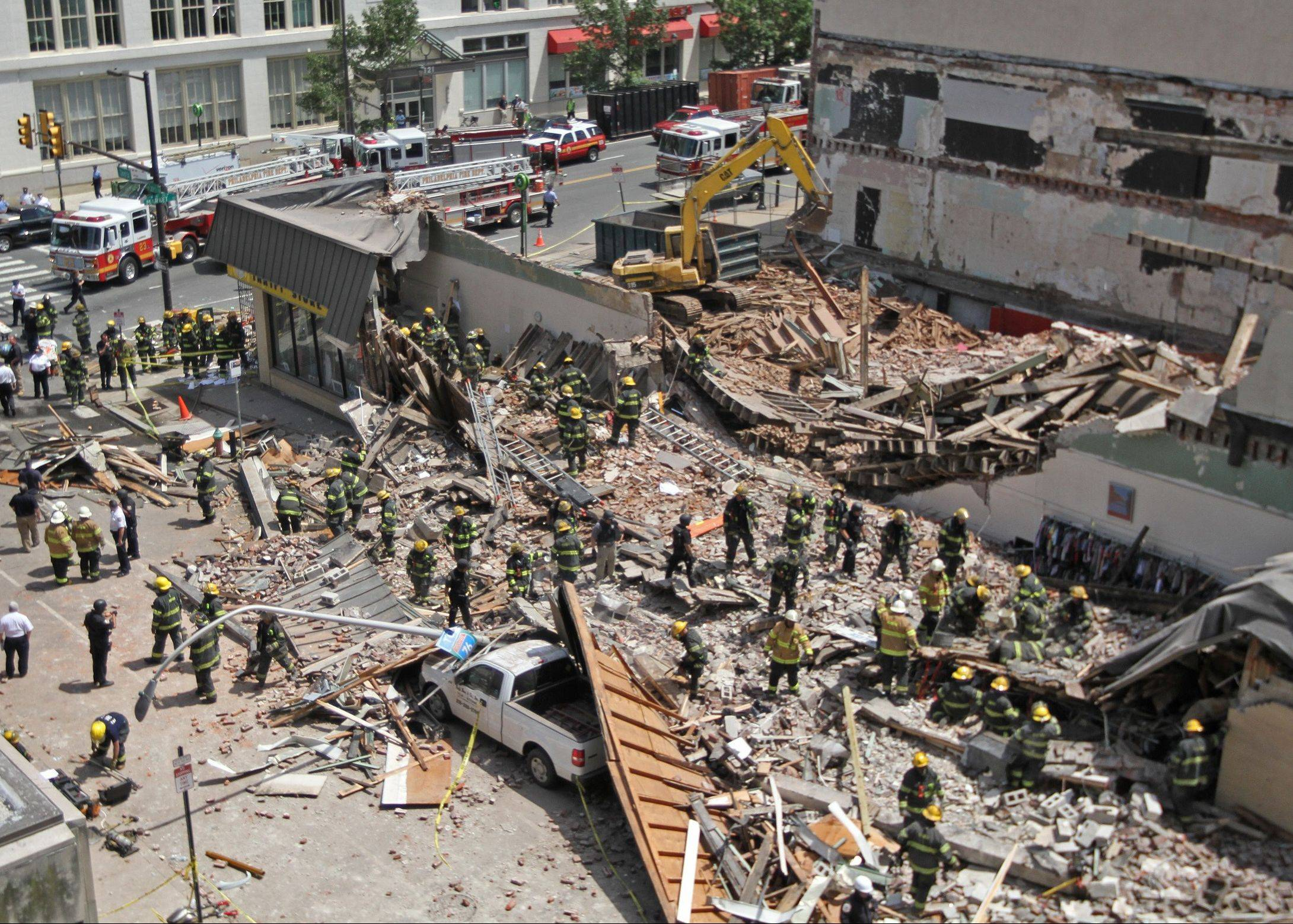 Rescue personnel search the scene of a building collapse Wednesday in downtown Philadelphia.