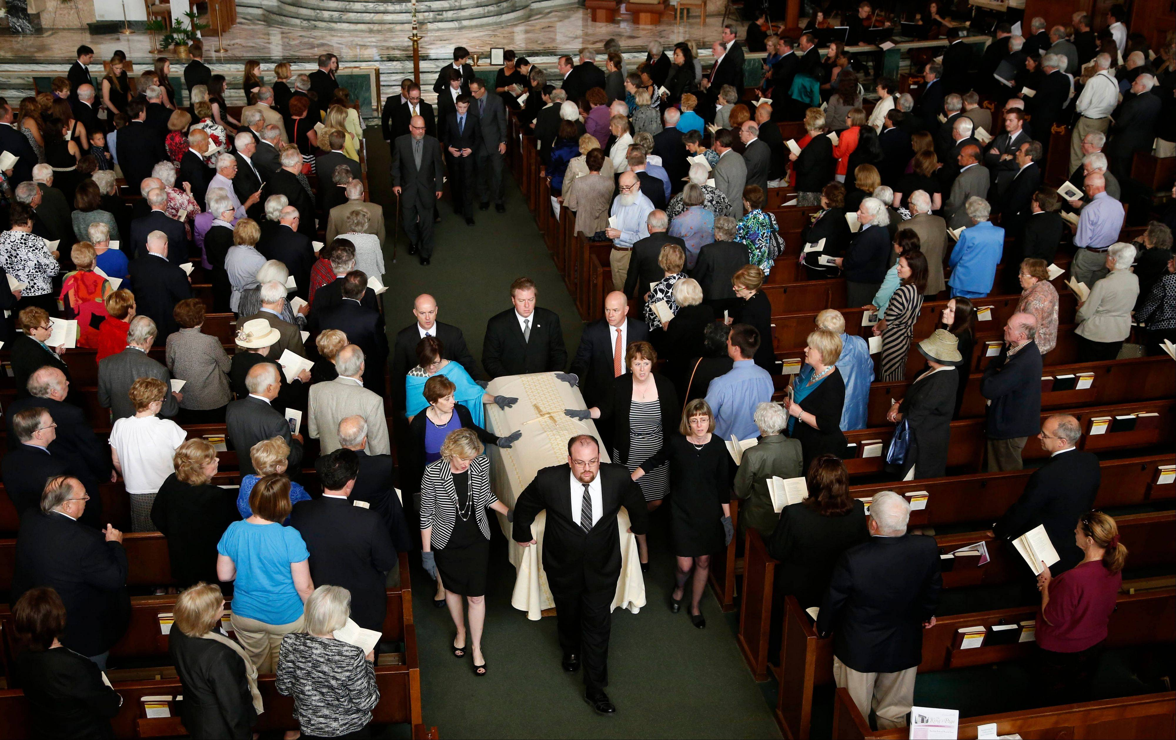 Family members of the Rev. Andrew Greeley lead the recessional after a funeral Mass for Greeley at Christ The King Church Wednesday, June 5, 2013, in Chicago. Greeley, an outspoken priest and best-selling author died in his Chicago home last week he was 85.
