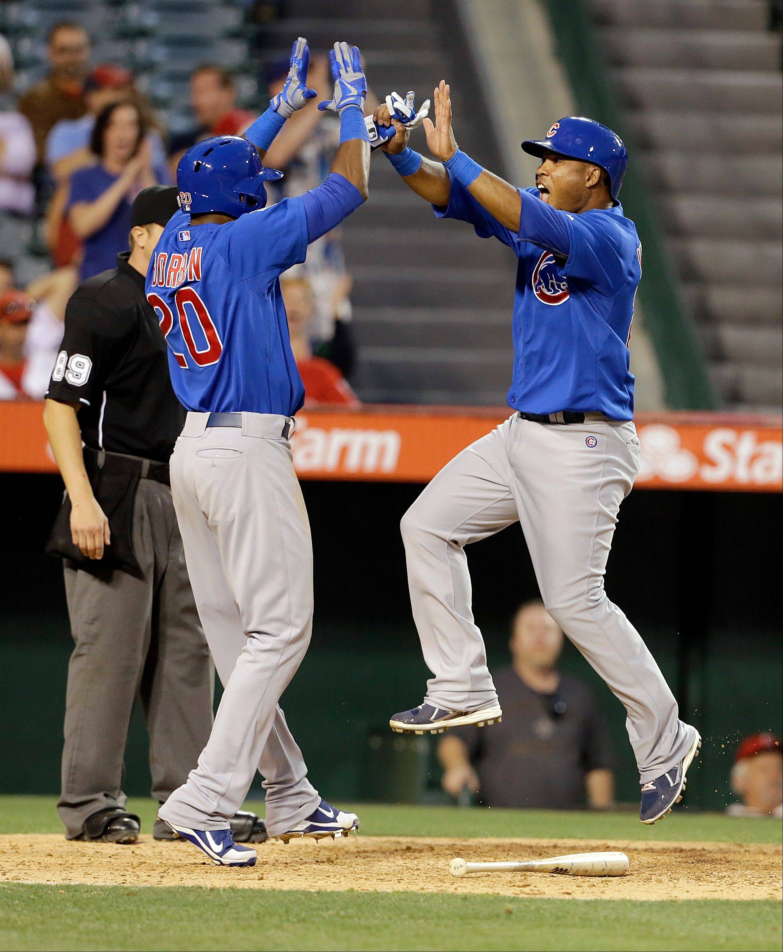 Chicago Cubs Julio Borbon, left, and Luis Valbuena, two of three runners who scored on a an Anthony Rizzo double, celebrate in the tenth inning against the Los Angeles Angels in a baseball game in Anaheim, Calif., Wednesday, June 5, 2013.