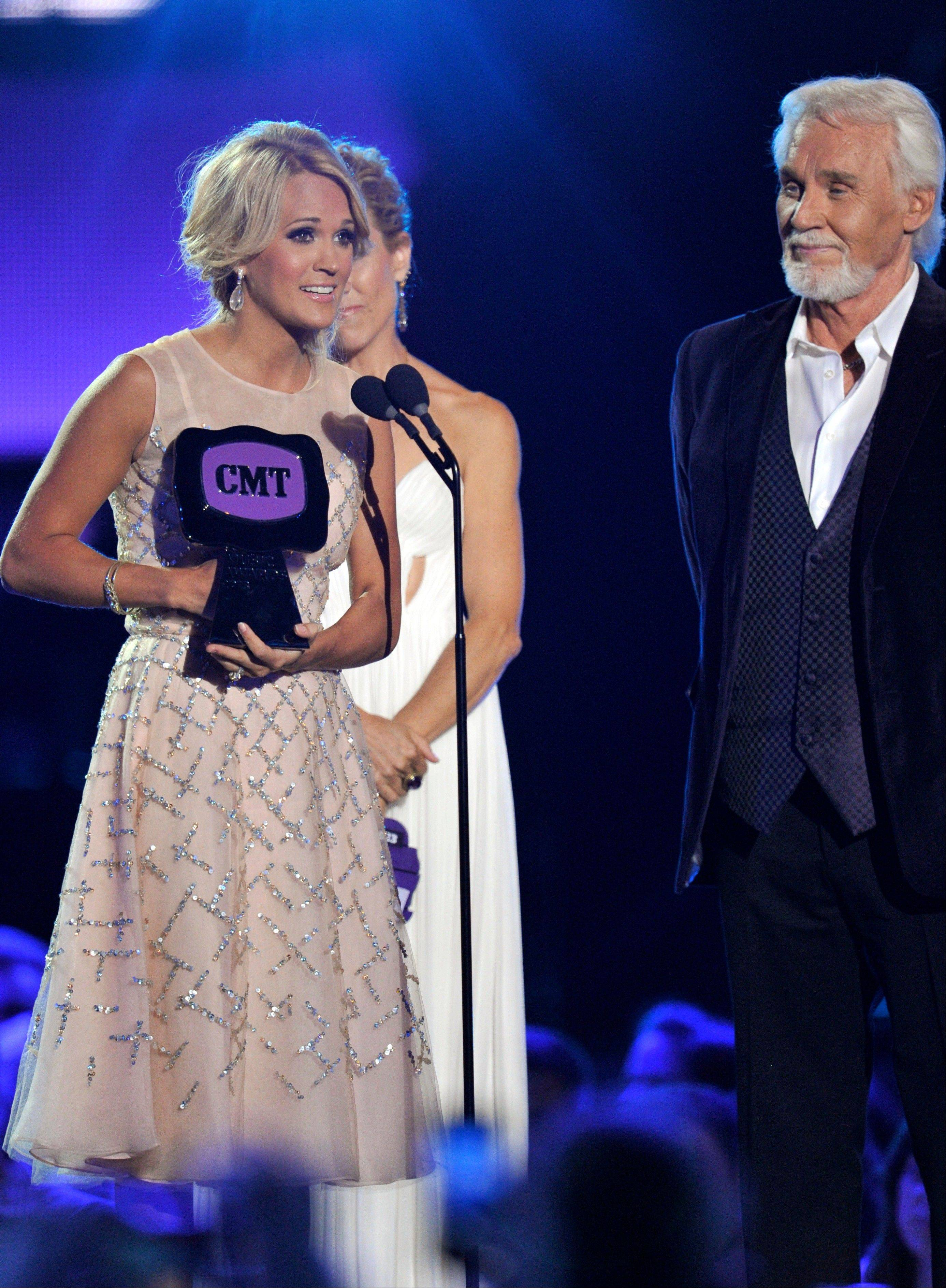 "Carrie Underwood, left, accepts the award for video of the year for ""Blown Away"" at the 2013 CMT Music Awards at Bridgestone Arena on Wednesday in Nashville, Tenn. Kenny Rogers presented her with the award."