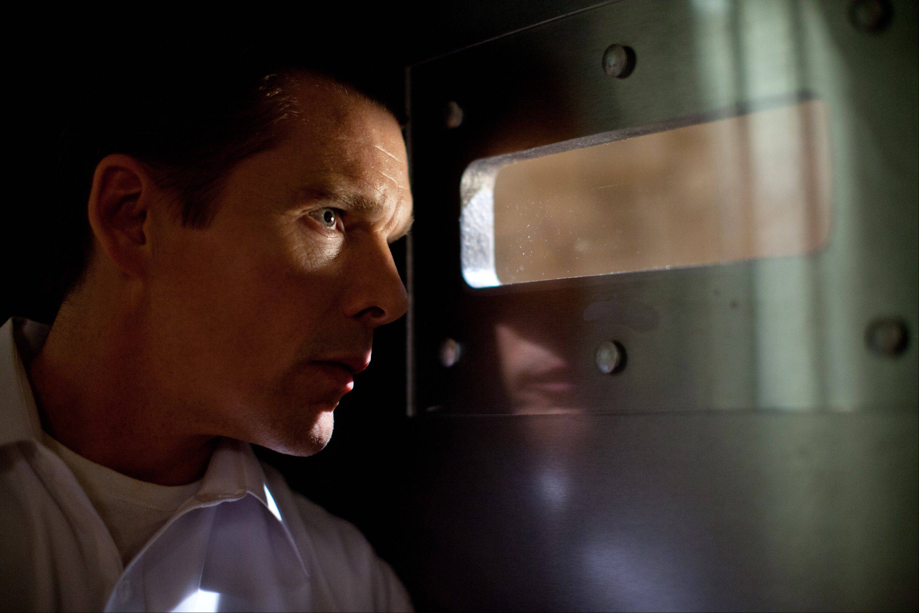 "James (Ethan Hawke) watches the horror unfold outside his home in ""The Purge."""