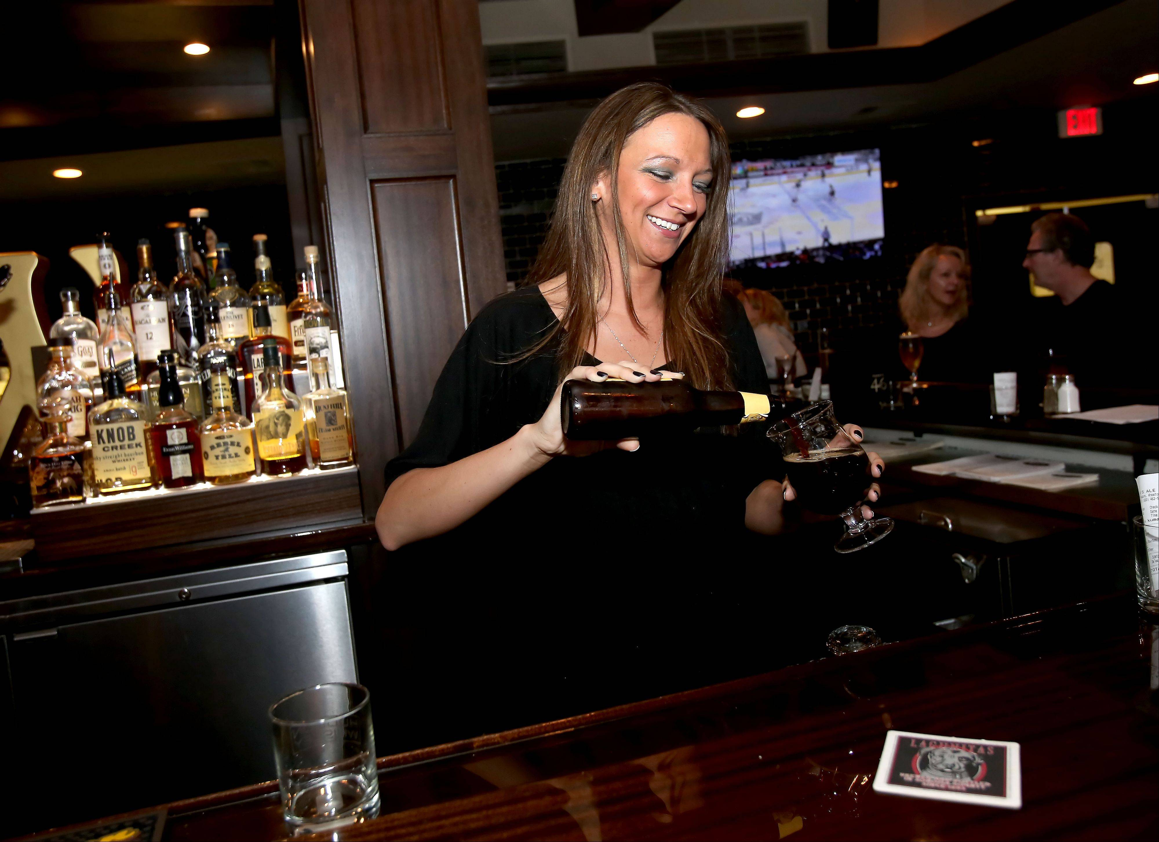 Bartender Jackie Elizondo pours a beer at Warren's Ale House in Wheaton.