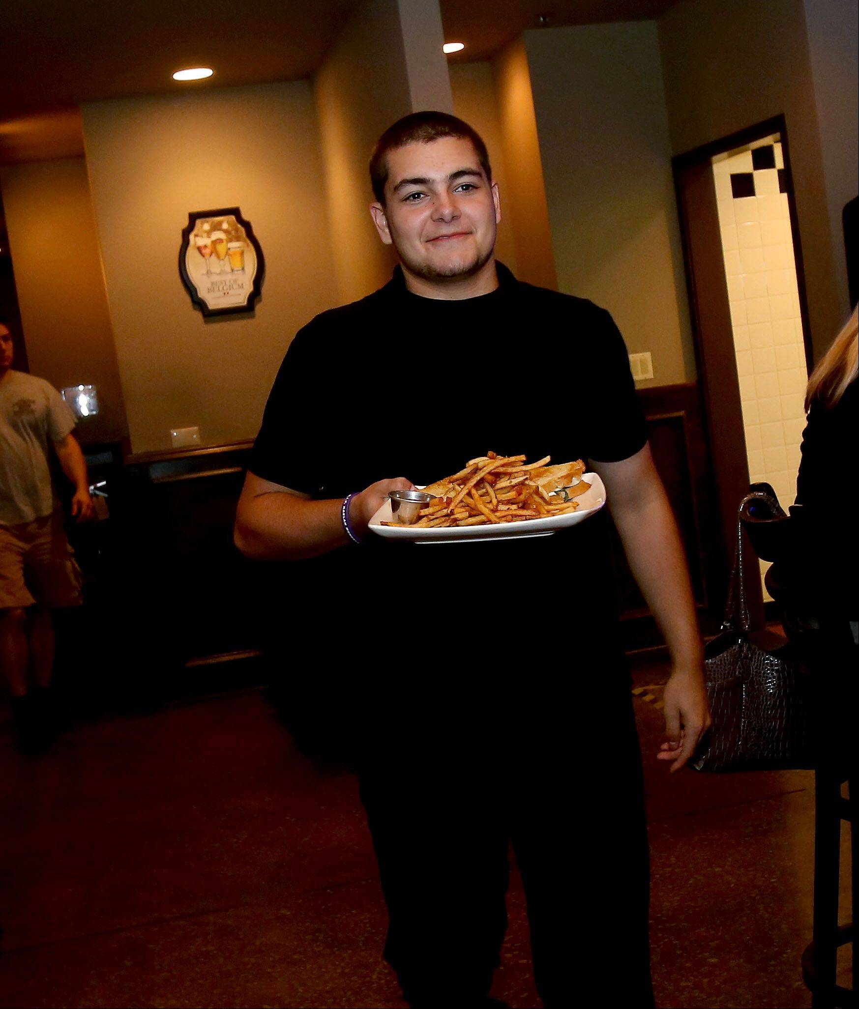 Mike Monaco brings out a plate of food at Warren's Ale House in Wheaton.
