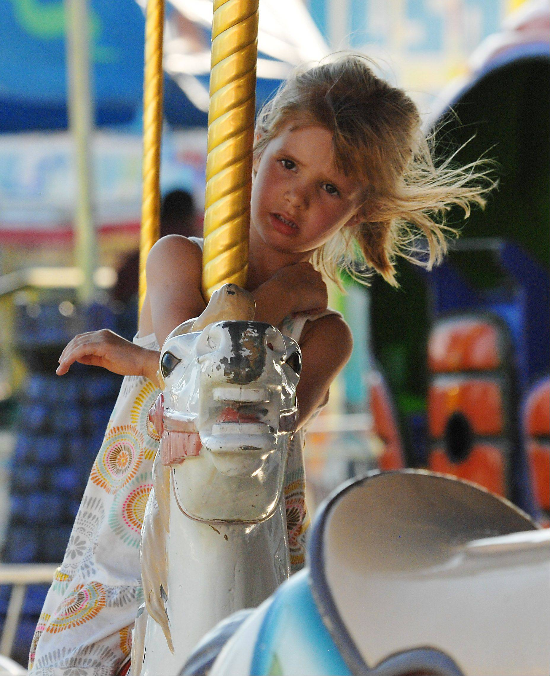 Reagan Malone of Elk Grove Village holds on for dear life as she rides the merry-go-round at last year's Rotaryfest in Elk Grove Village.