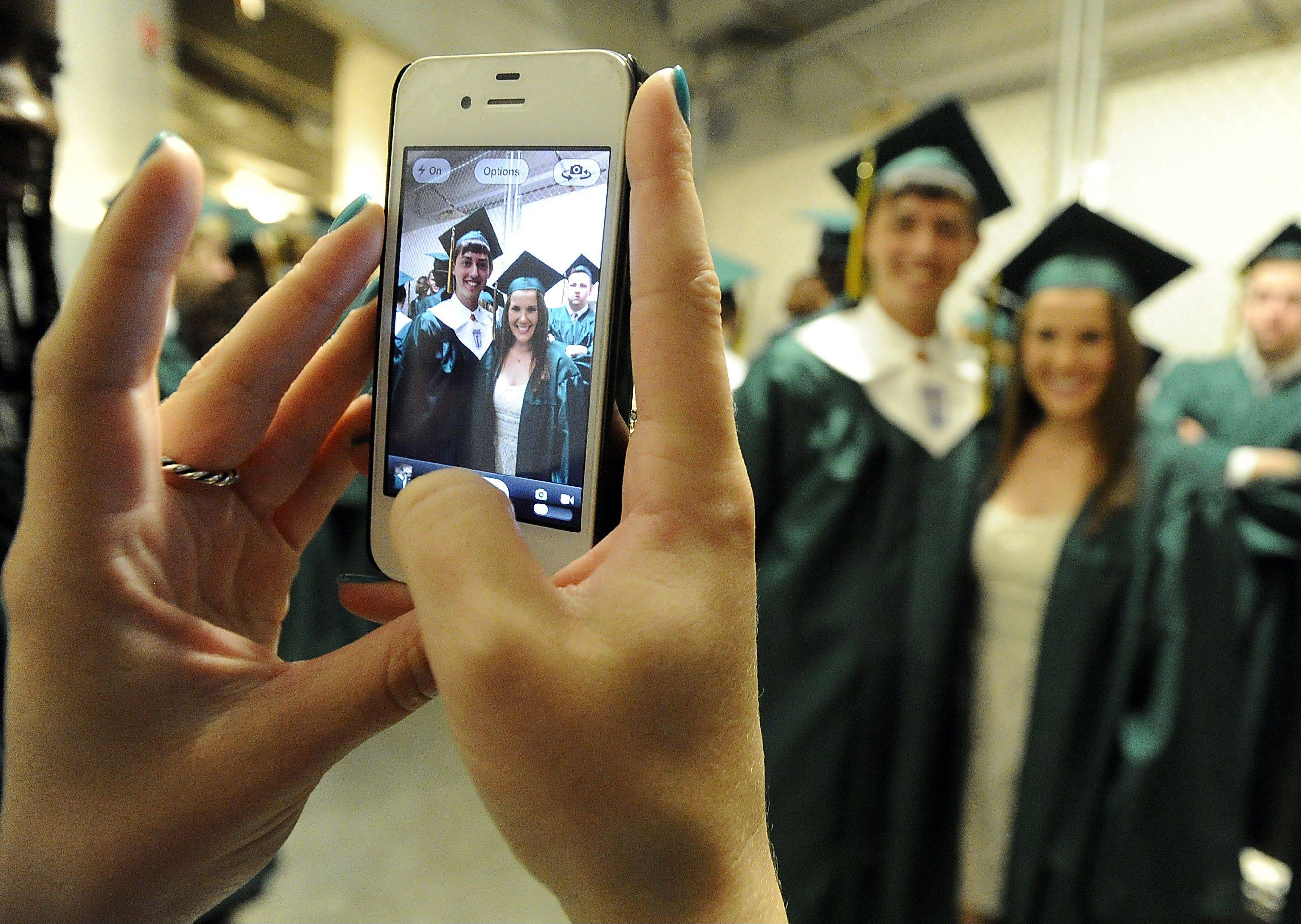 Melanie Bresler,18, and Scott Feldman,18, both of Buffalo Grove get their picture taken before their graduation by fellow classmate Kari Antman,18, of Buffalo Grove at the Stevenson High School Commencement Program at the Sears Centre on Thursday.