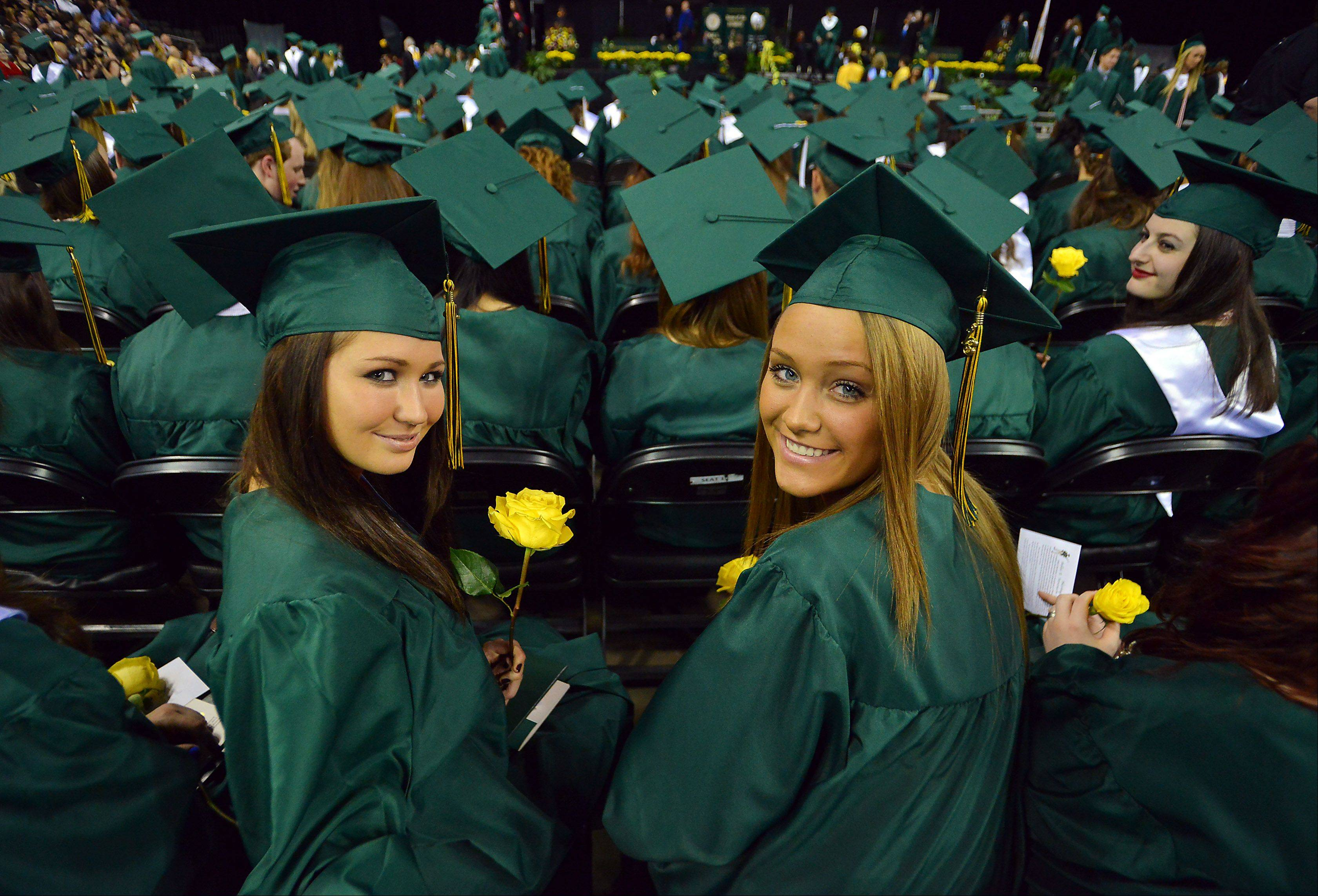 Left to right, Kellienne Sita,18, of Kildeer and Monika Smolen,18, of Buffalo Grove participate in the Stevenson High School Commencement Program at the Sears Centre on Thursday.