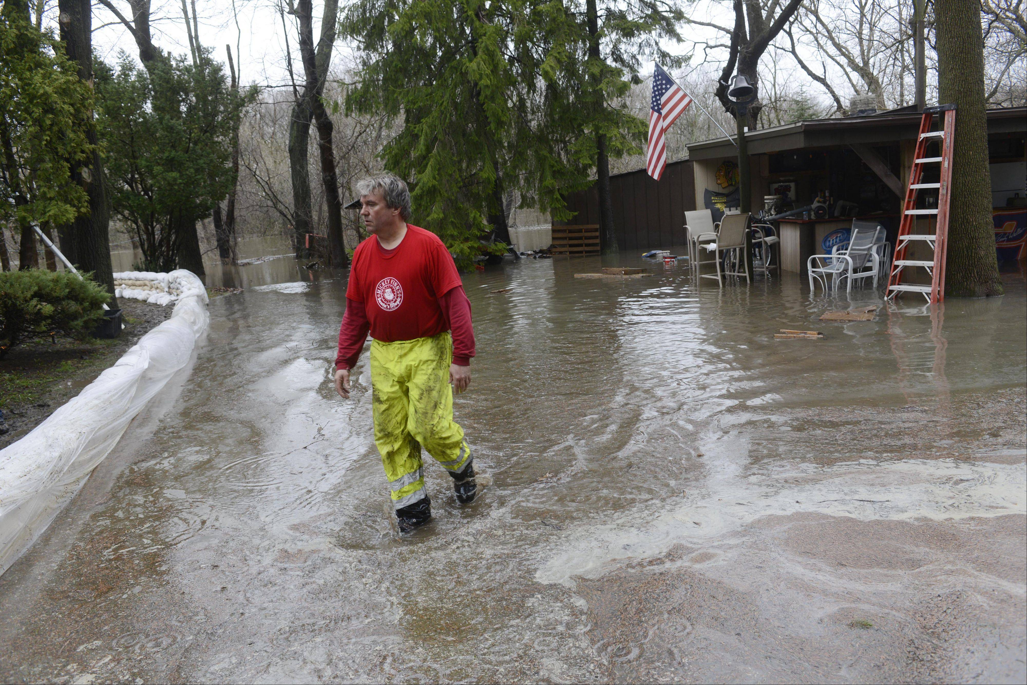 James Eck walks toward his house during the construction of a sandbag wall in the flooded Big Bend neighborhood in Des Plaines in April. Some suburban counties qualified for more federal flood aid Thursday, but Cook County wasn't among them.