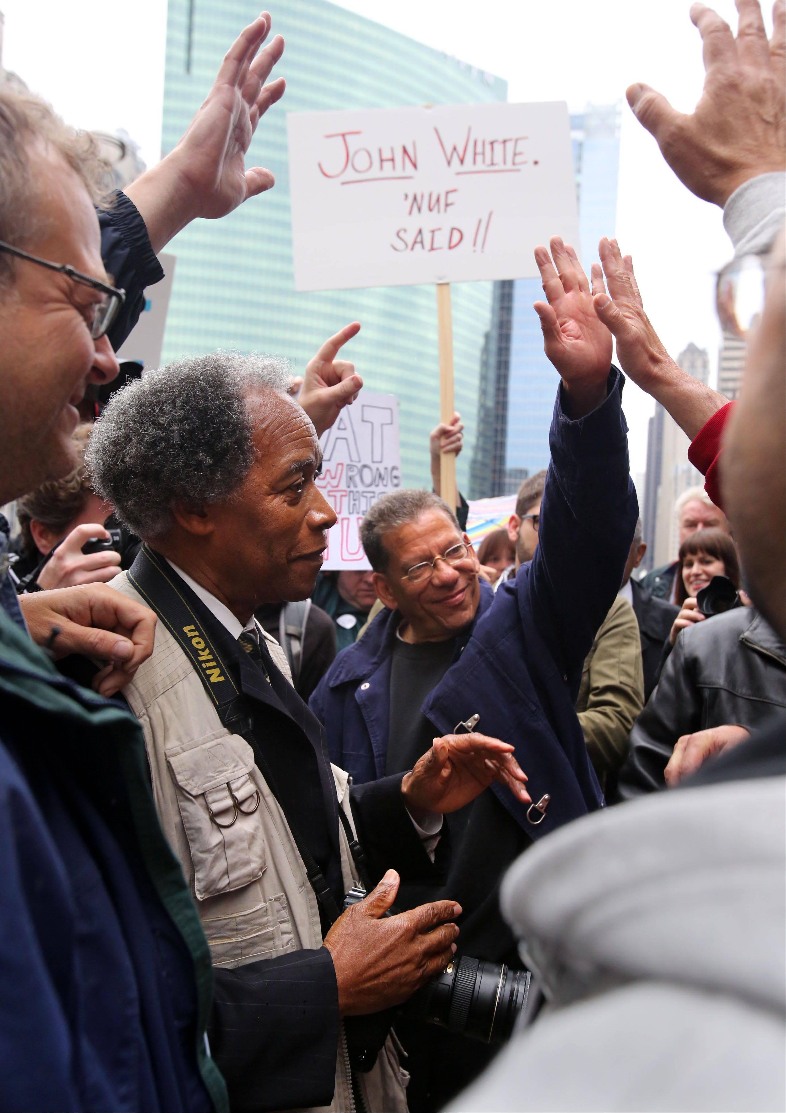 John H. White, second from left, who won a Pulitzer in 1982, and other former Sun-Times photographers high-five after about 150 supporters marched in front of the Chicago Sun-Times building in Chicago Thursday. The rally was organized by the Chicago Newspaper Guild in response to the paper cutting its photography staff.