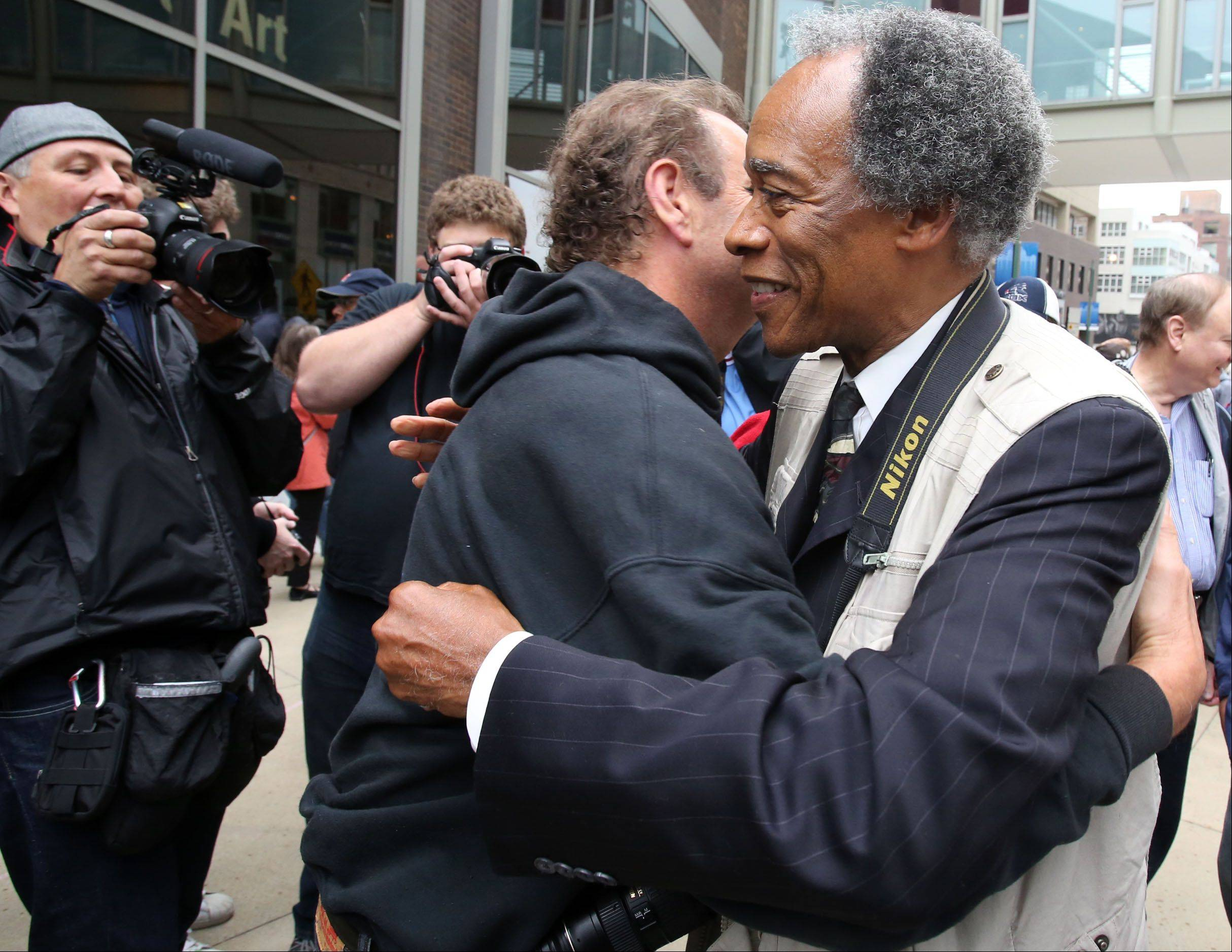Former Sun-Times photographer John H. White, right, gets a hug from photographer Rich Chapman as about 150 rally in front of the Chicago Sun-Times building in support of the 28 laid-off photographers from the Sun-Times and its suburban newspapers.