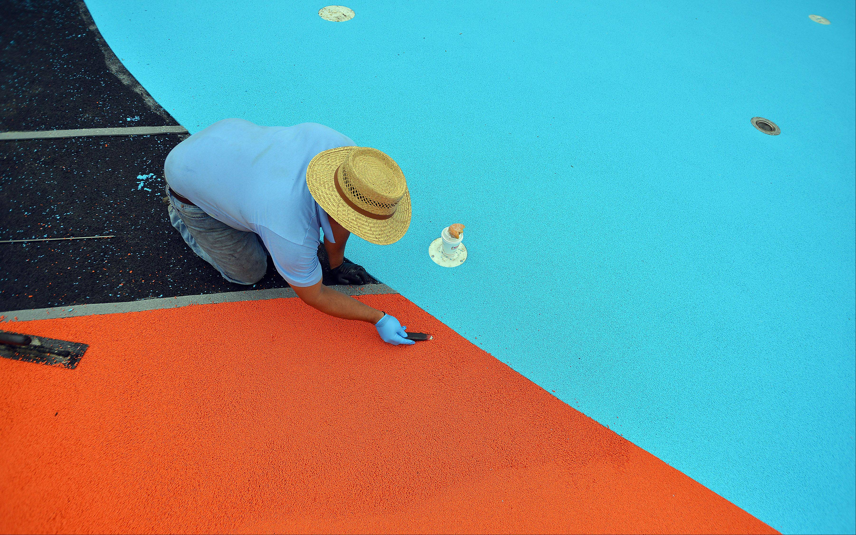 A worker painstakingly removes the blue beads from the orange group as he lays down the surface for the new splash pad Wednesday at the Rolling Meadows pool complex.