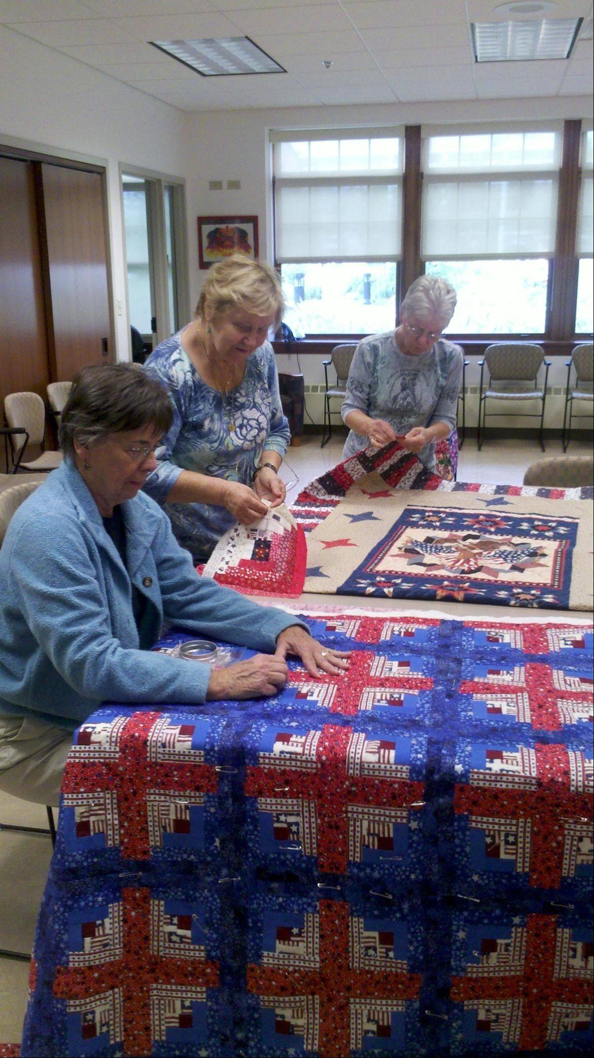 "Members of the Mount Prospect-based Sew Bee It quilting club work on one of the 10 ""valor quilts"" they'll be giving to local veterans next week. Club members spent eight months preparing the quilts, which carry patriotic themes."
