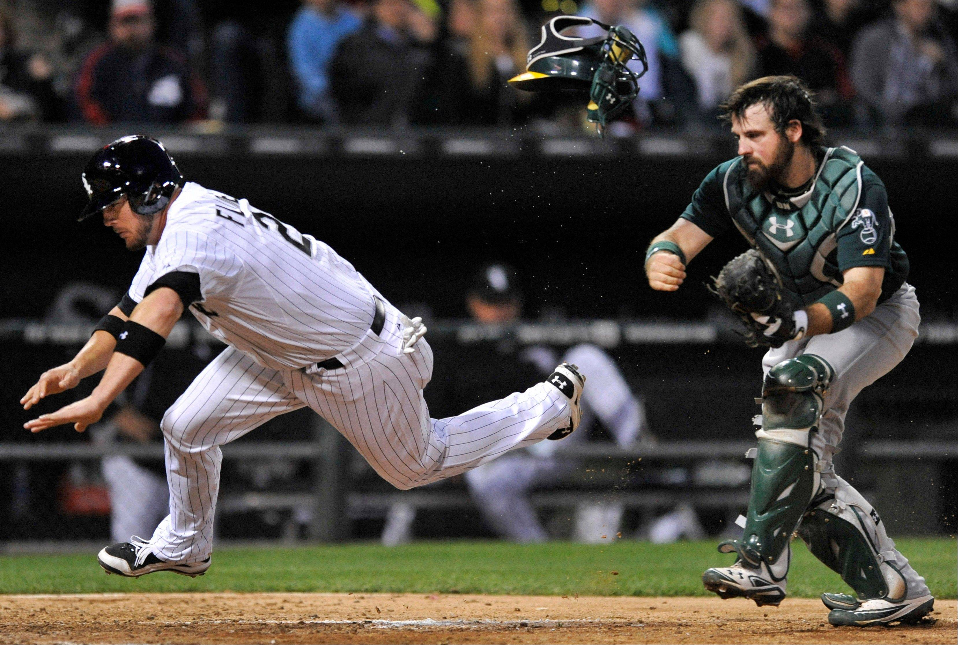 Chicago White Sox's Tyler Flowers left, is tagged out at home plate by Oakland Athletics catcher Derek Norris during the fifth inning of a baseball game in Chicago, Thursday, June 6, 2013.