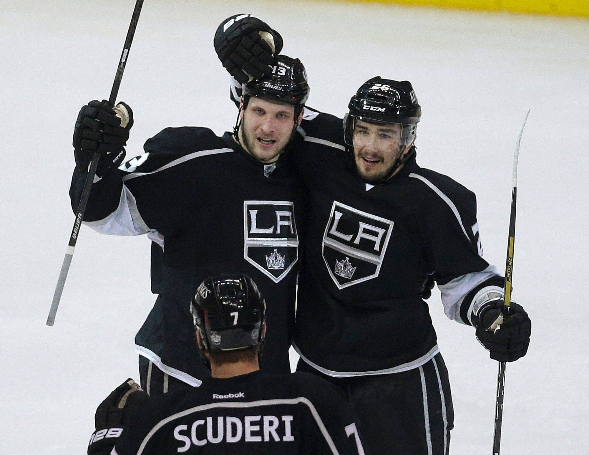 Los Angeles Kings defenseman Slava Voynov, right, celebrates with Kyle Clifford and Rob Scuderi after his goal against the Chicago Blackhawks during the first period in Game 4 of the NHL hockey Stanley Cup Western Conference finals, in Los Angeles on Thursday, June 6, 2013.