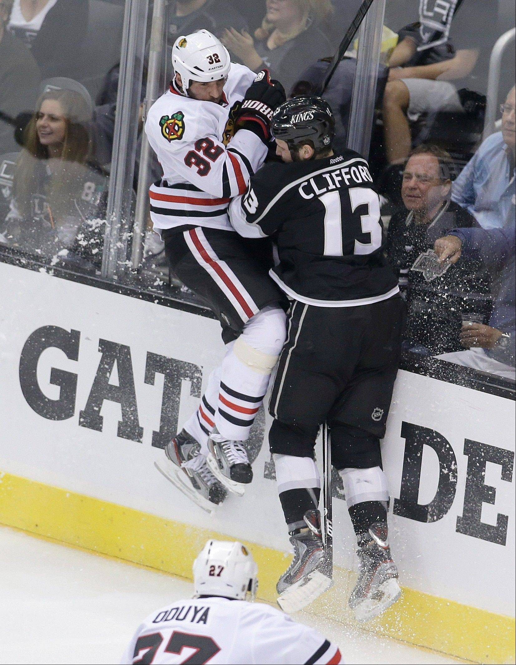 Los Angeles Kings left wing Kyle Clifford, right, checks Chicago Blackhawks defenseman Michal Rozsival during the first period in Game 4 of the NHL hockey Stanley Cup Western Conference finals, in Los Angeles on Thursday, June 6, 2013.
