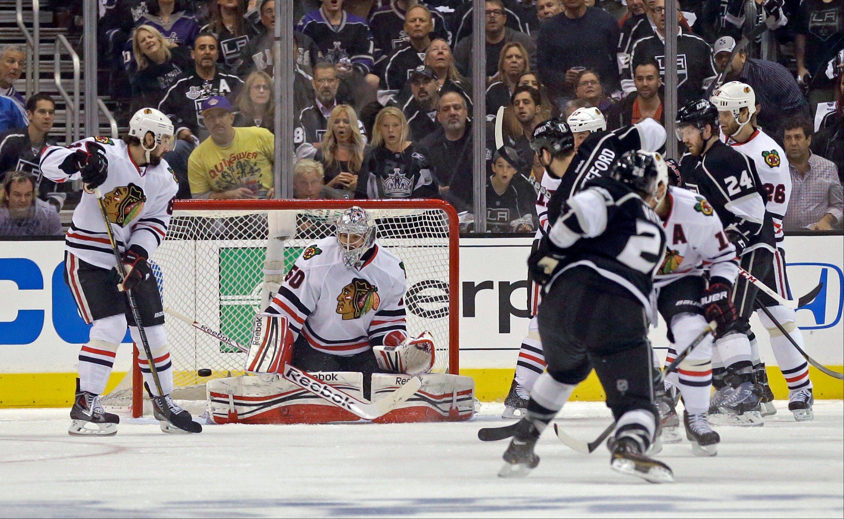 Los Angeles Kings defenseman Slava Yoynov, right front, of Russia, scores against Chicago Blackhawks goalie Corey Crawford (50) during the first period of Game 3 of the NHL hockey Stanley Cup playoffs Western Conference finals, in Los Angeles on Thursday, June 6, 2013.