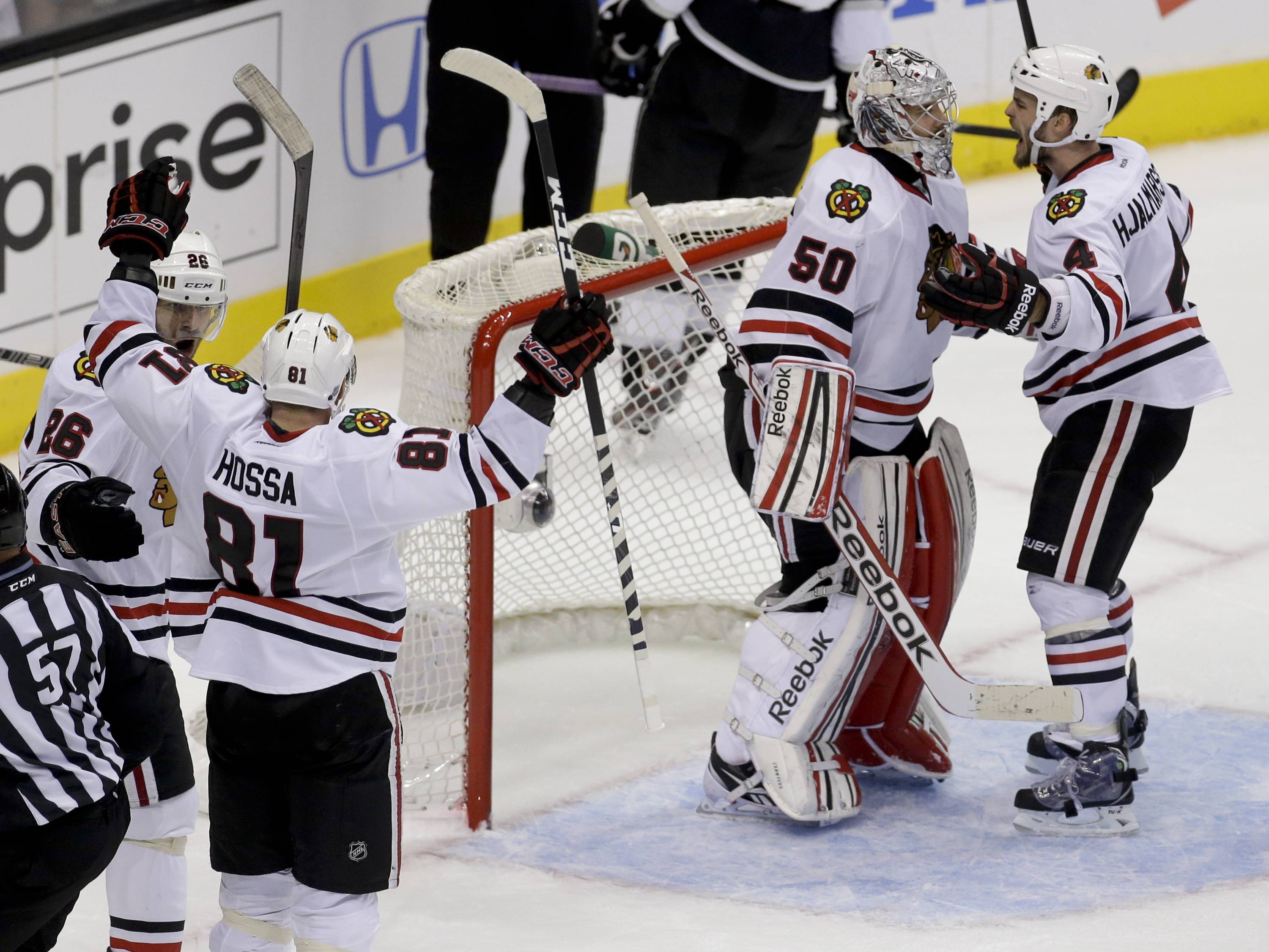 Chicago Blackhawks' Michal Handzus, Marian Hossa, goalie Corey Crawford, and Niklas Hjalmarsson, fromleft, celebrate a 3-2 win against the Los Angeles Kings in Game 4 of the NHL hockey Stanley Cup playoffs Western Conference finals, in Los Angeles on Thursday, June 6, 2013.