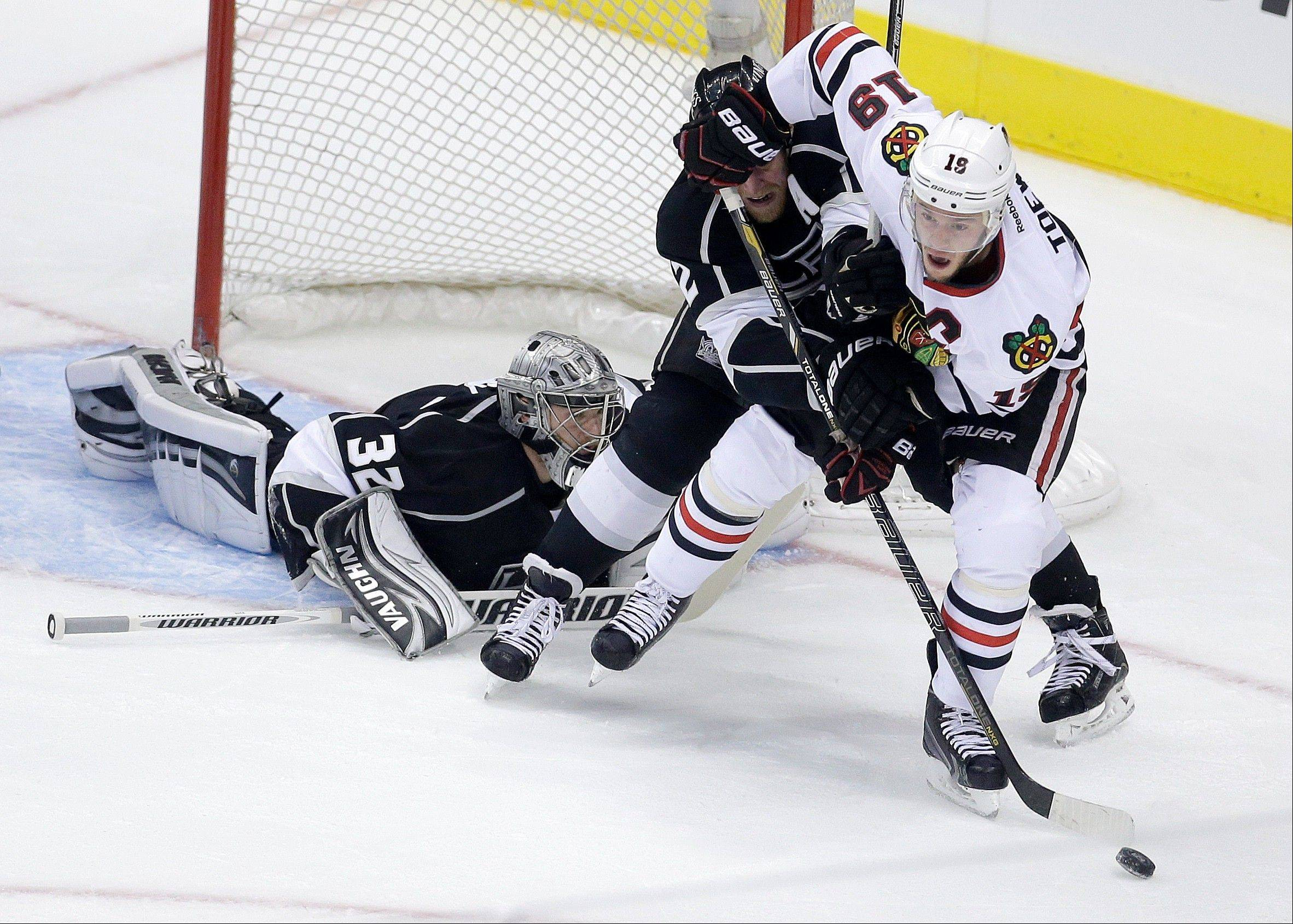 Chicago Blackhawks center Jonathan Toews, right, works the puck against Los Angeles Kings defenseman Matt Greene, middle, and goalie Jonathan Quick during the first period in Game 4 of the NHL hockey Stanley Cup playoffs Western Conference finals, in Los Angeles on Thursday, June 6, 2013.