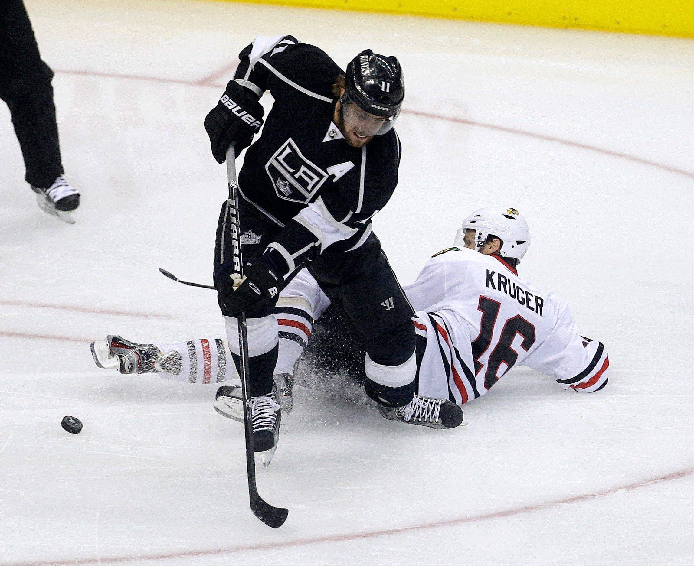 Los Angeles Kings center Anze Kopitar, top, knocks the puck way from Chicago Blackhawks center Marcus Kruger during the first period in Game 4 of the NHL hockey Stanley Cup playoffs Western Conference finals, in Los Angeles on Thursday, June 6, 2013.