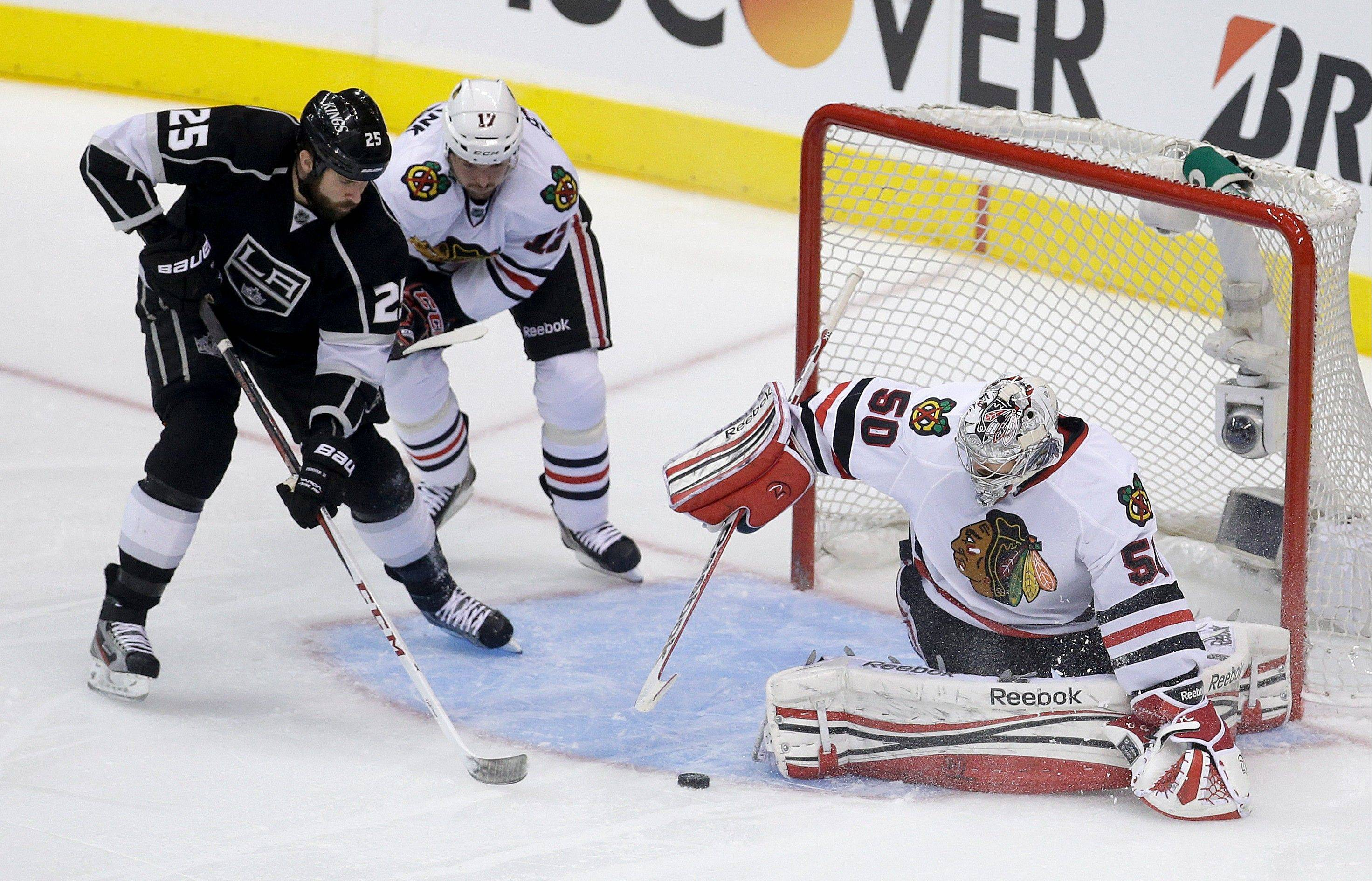 Los Angeles Kings left wing Dustin Penner, left, scores past Chicago Blackhawks goalie Corey Crawford, right, and Blackhawks' Sheldon Brookbank during the second period in Game 4 of the NHL hockey Stanley Cup playoffs Western Conference finals, in Los Angeles on Thursday, June 6, 2013.