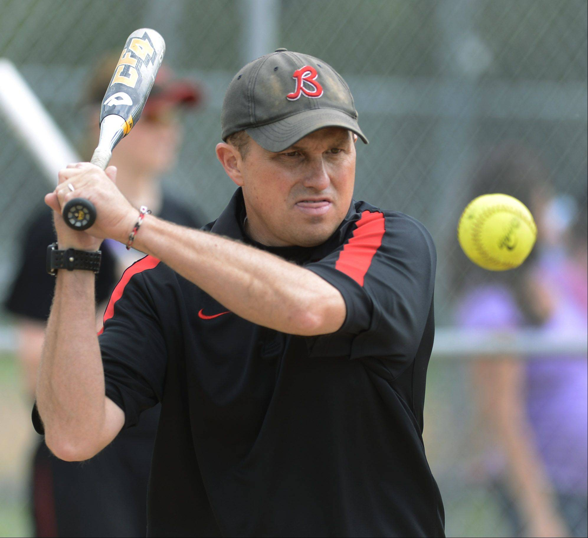 Barrington softball coach Perry Peterson hits groundballs during infield warm-ups before the Fillies' sectional final victory over New Trier.