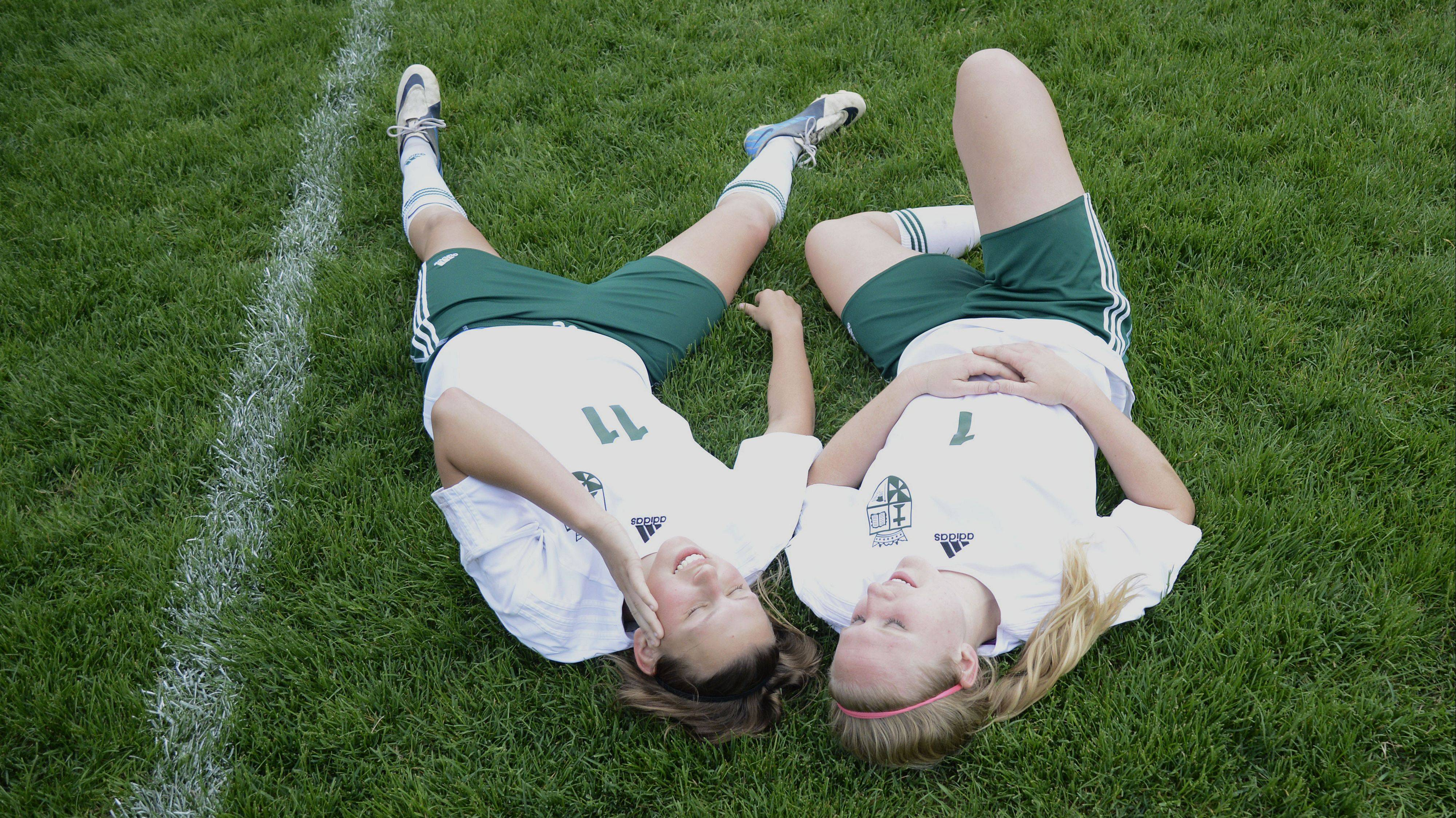 St. Edward's Corey Lepoudre, right, relaxes with teammate Allison Kruk while teammates take photos after their Class 1A sectional title game win over Willows Academy. Lepoudre is the honorary captain of the 2013 Fox Valley all-area team for girls soccer.