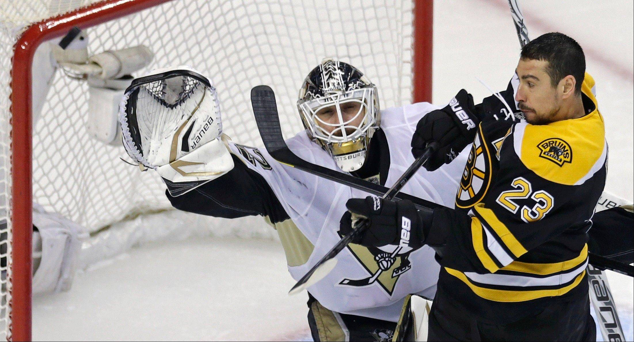 Boston Bruins center Chris Kelly tries to get the stick on the puck as Pittsburgh Penguins goalie Tomas Vokoun raises his glove to make a save during overtime in Game 3 of the NHL hockey Stanley Cup playoffs Eastern Conference finals, in Boston on Wednesday.