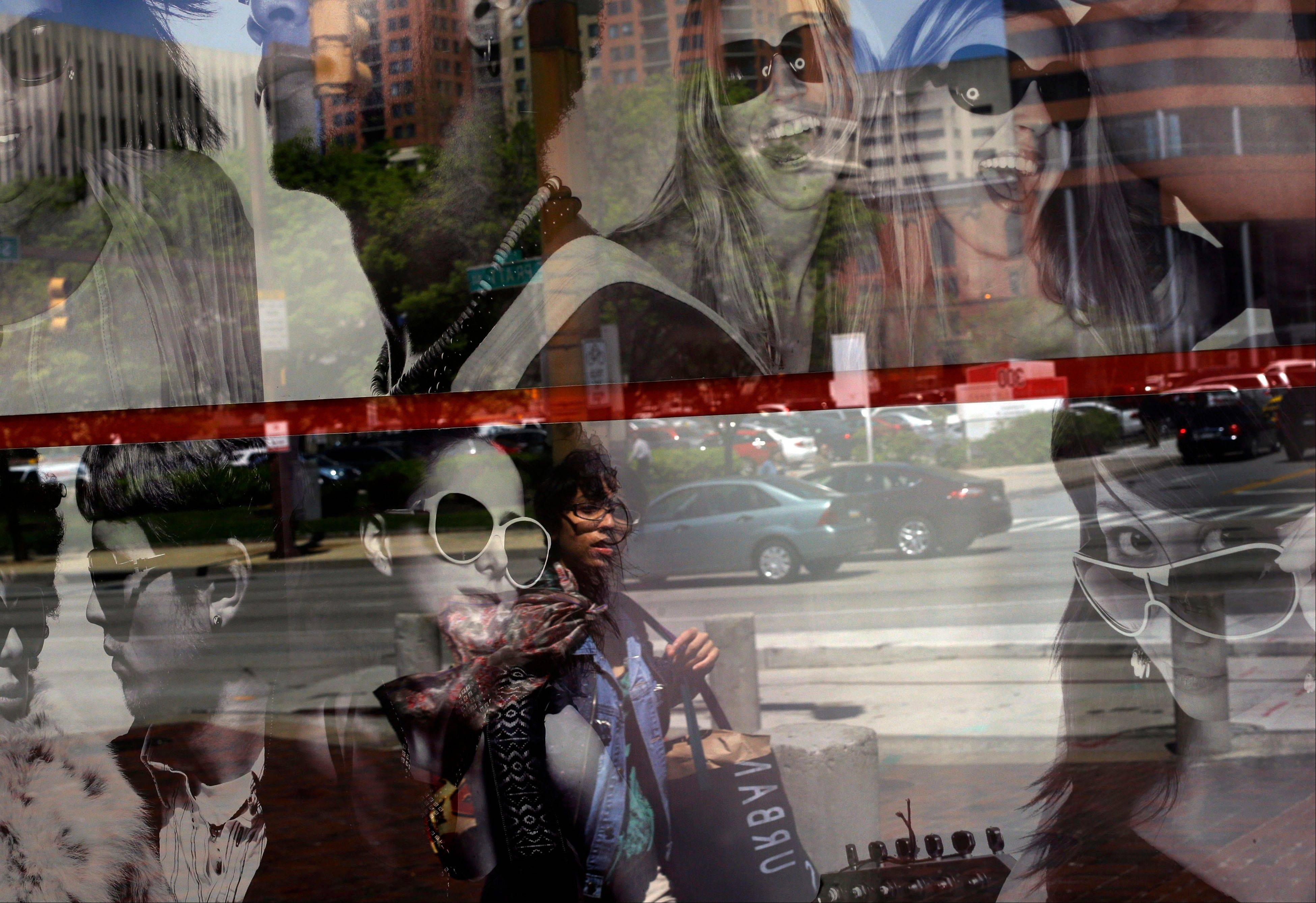 A woman is reflected in a retail store�s window display in Baltimore. The Federal Reserve reported Friday how much consumers borrowed in April.