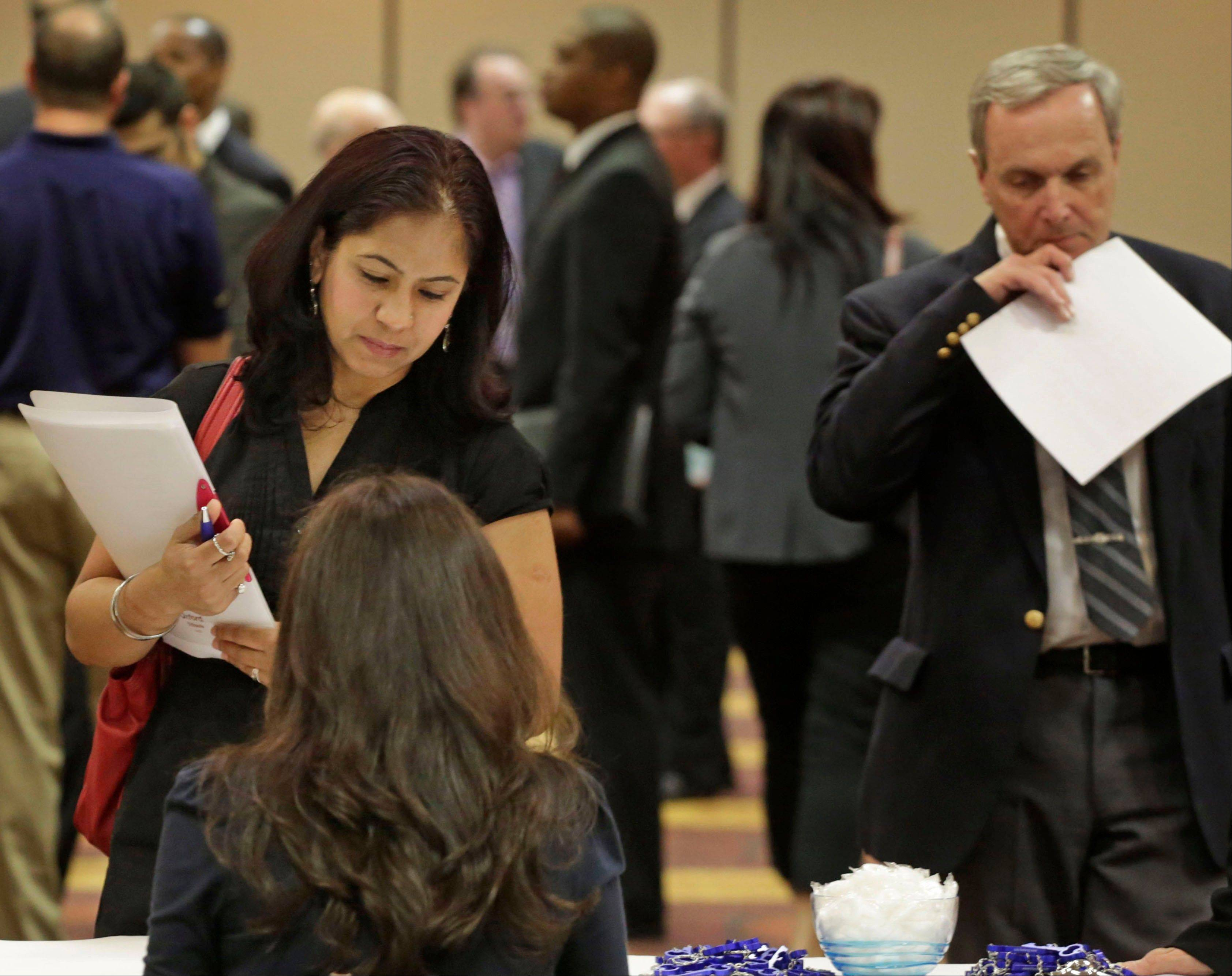 Jobseeker Anu Vatal of Chicago speaks with Patrice Tosi of BluePay, seated, during a career fair in Rolling Meadow. The government The Labor Department said Friday that the unemployment rate rose to 7.6 percent from 7.5 percent in April.