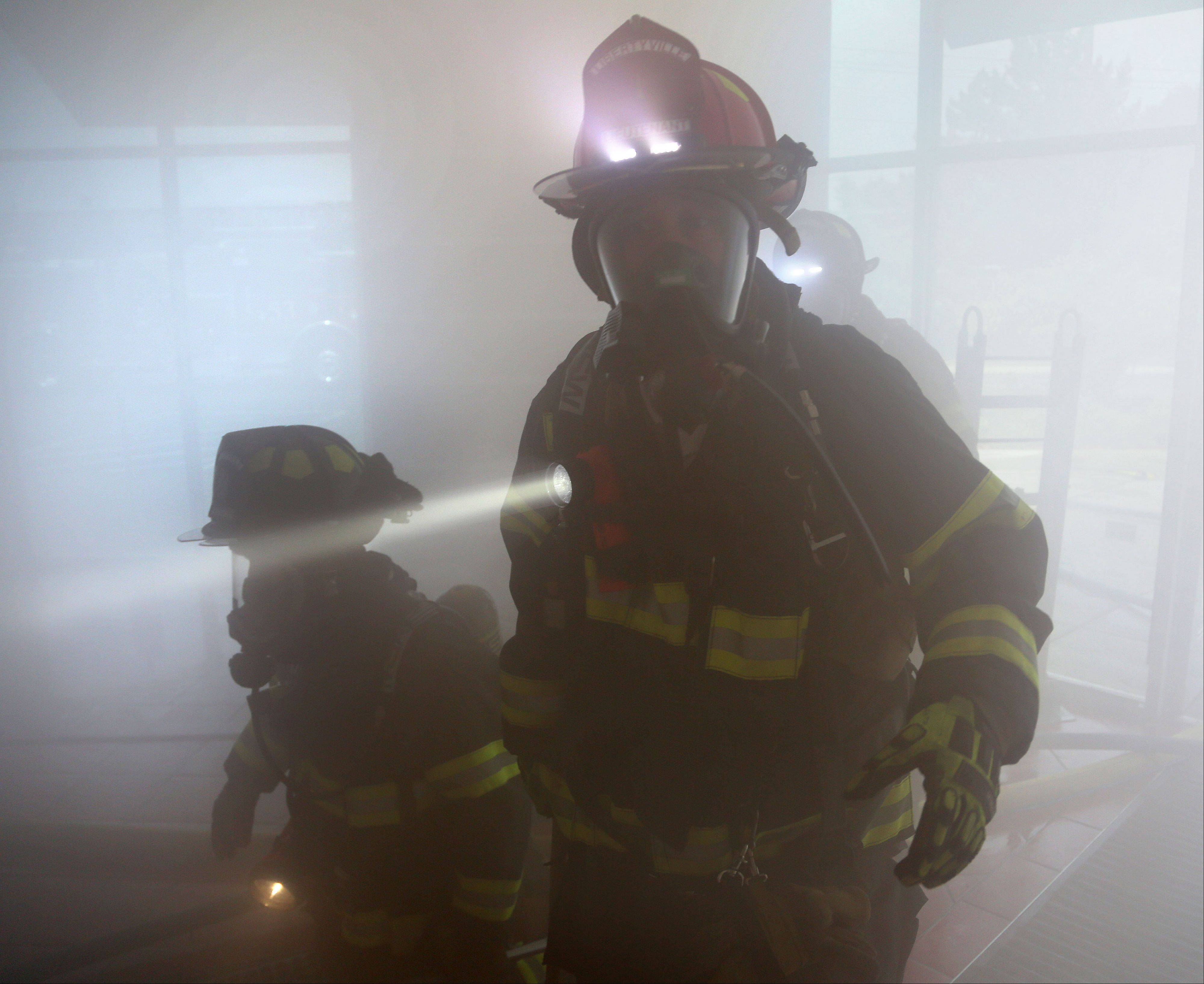 Countryside firefighters maneuver through a smoke filled building during search and rescue training Friday morning at the former Pier 1 Imports building in Vernon Hills.
