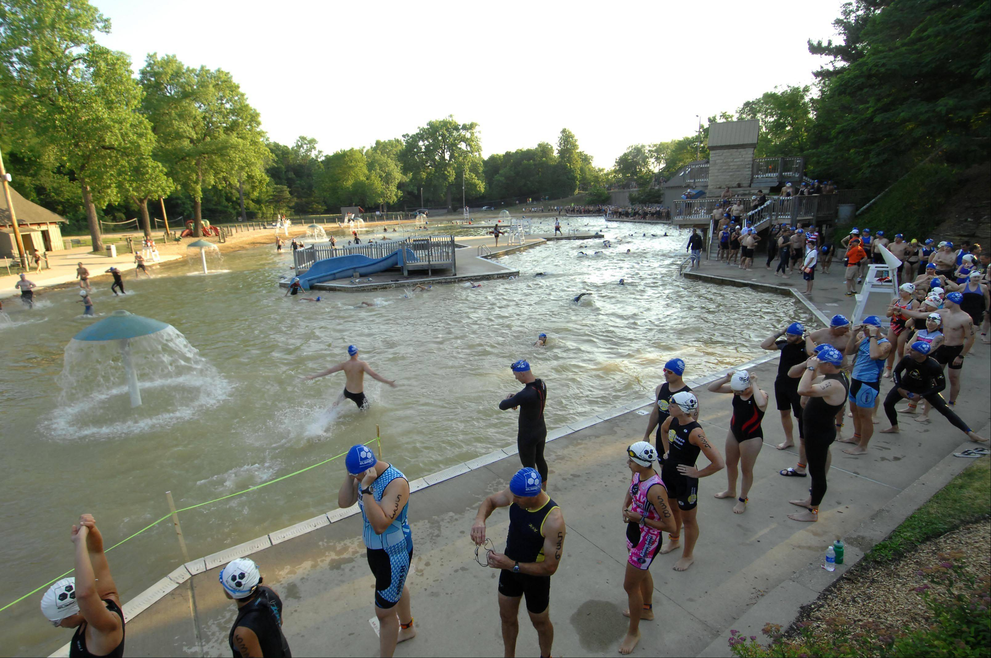 The line of competitors advances to the starting line as racers enter the water one by one at Quarry Beach at last year�s Batavia Triathlon and Duathlon.