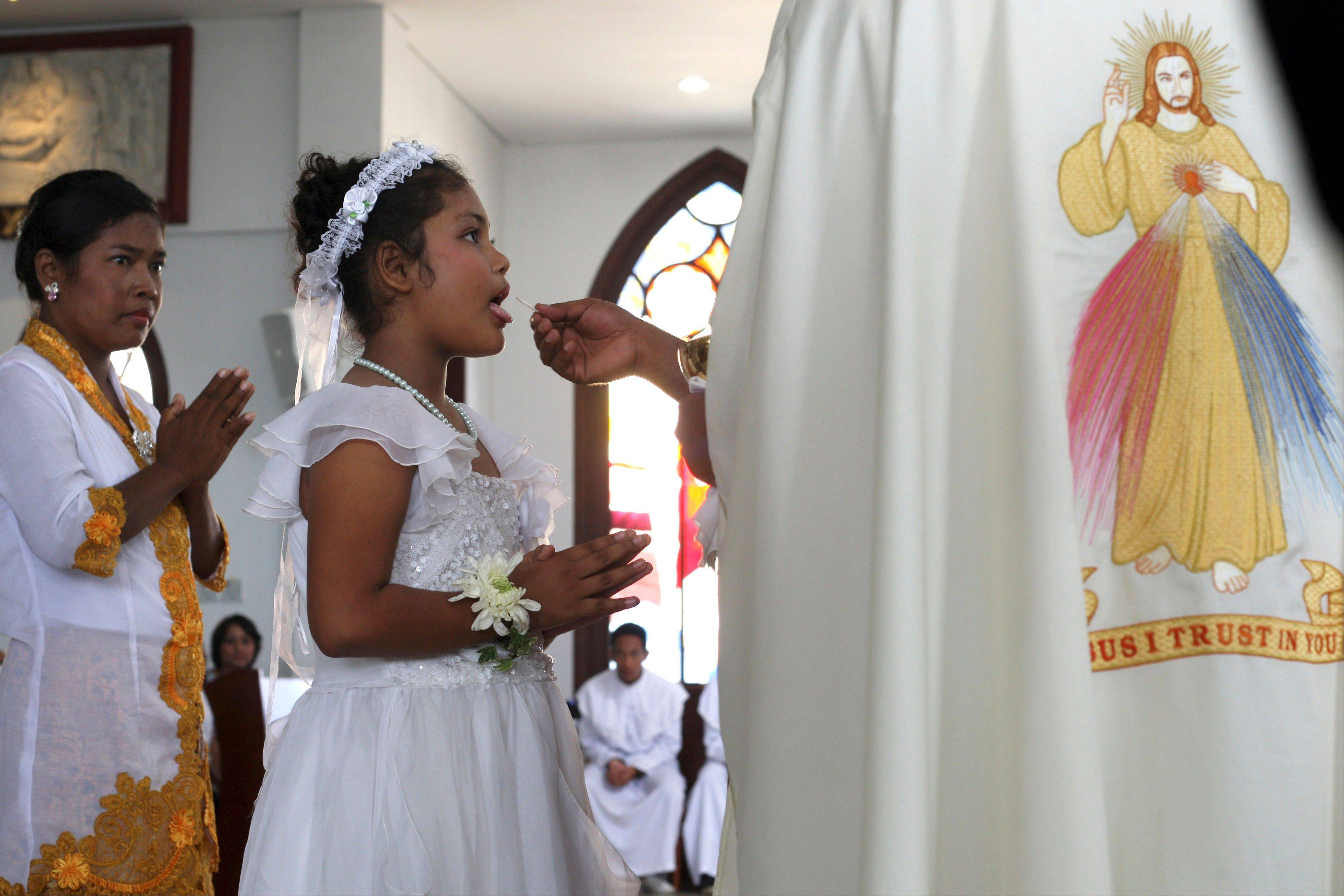 A girl receives communion during a mass for receiving the first communion at Catholic church in Nusa Dua, Bali, Indonesia. Indonesia's president has accepted a statesmanship award ofrom a U.S. interfaith foundation that says it hopes to encourage him to promote freedom of worship and tolerance in the world's most populous Muslim-majority nation.