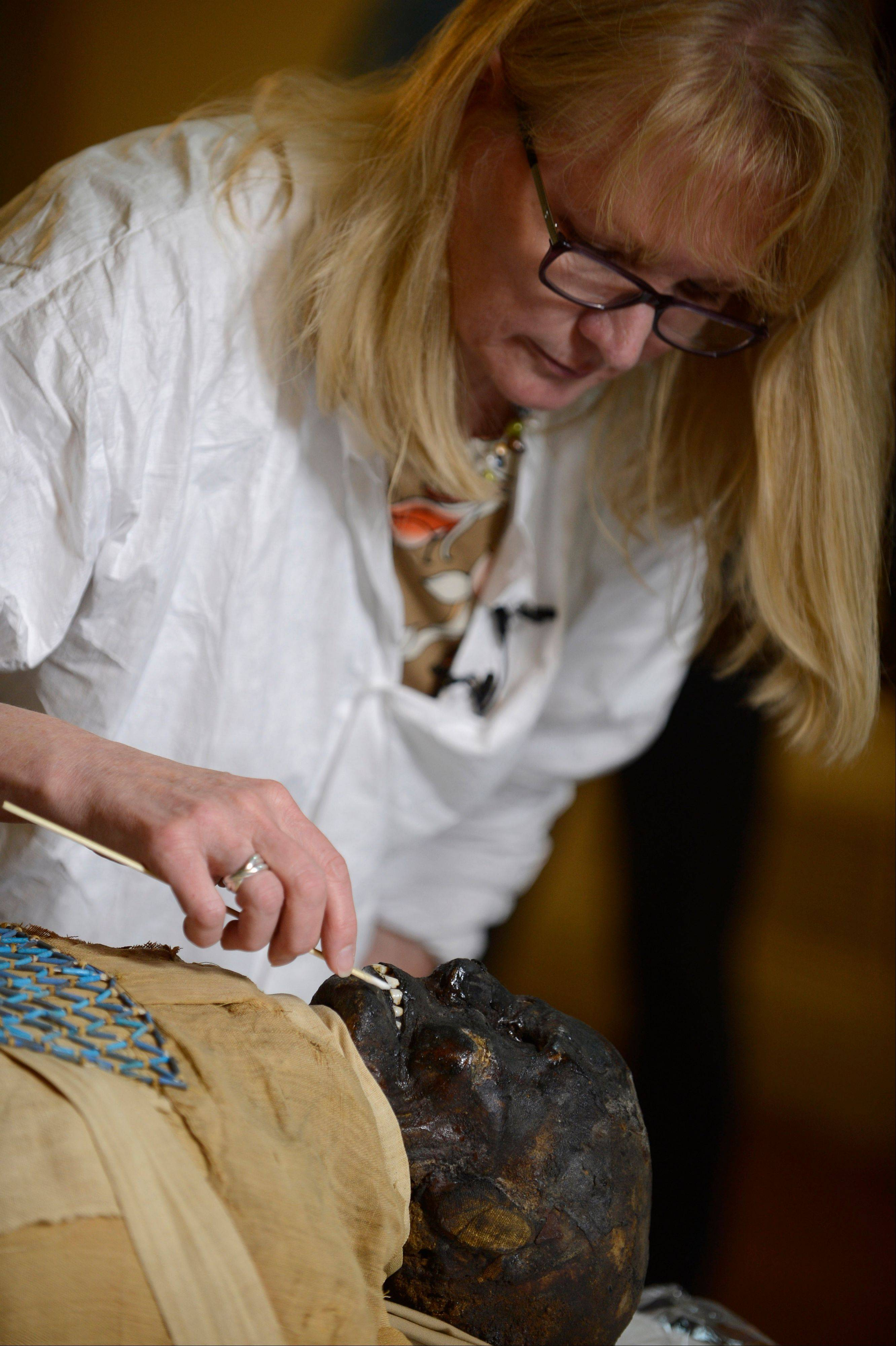 Mimi Leveque, a freelance conservator, cleans Padihershef, a 2,500-year-old Egyptian mummy at Mass General Hospital in Boston, on Friday.