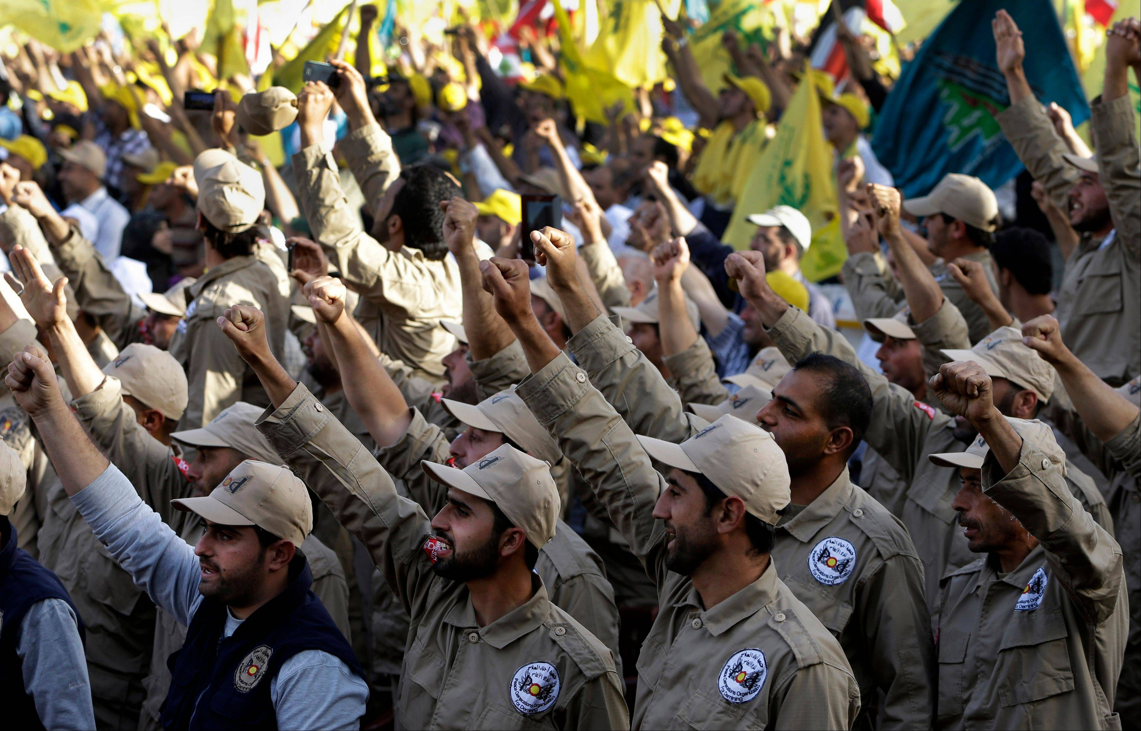"Associated Press/May 25, 2013 Members of the demining unit of Hezbollah raise up their hands as they shout slogans in support of pro-Hezbollah leader Sheik Hassan Nasrallah, during a rally commemorating ""Liberation Day,"" which marks the withdrawal of the Israeli army from southern Lebanon in 2000."