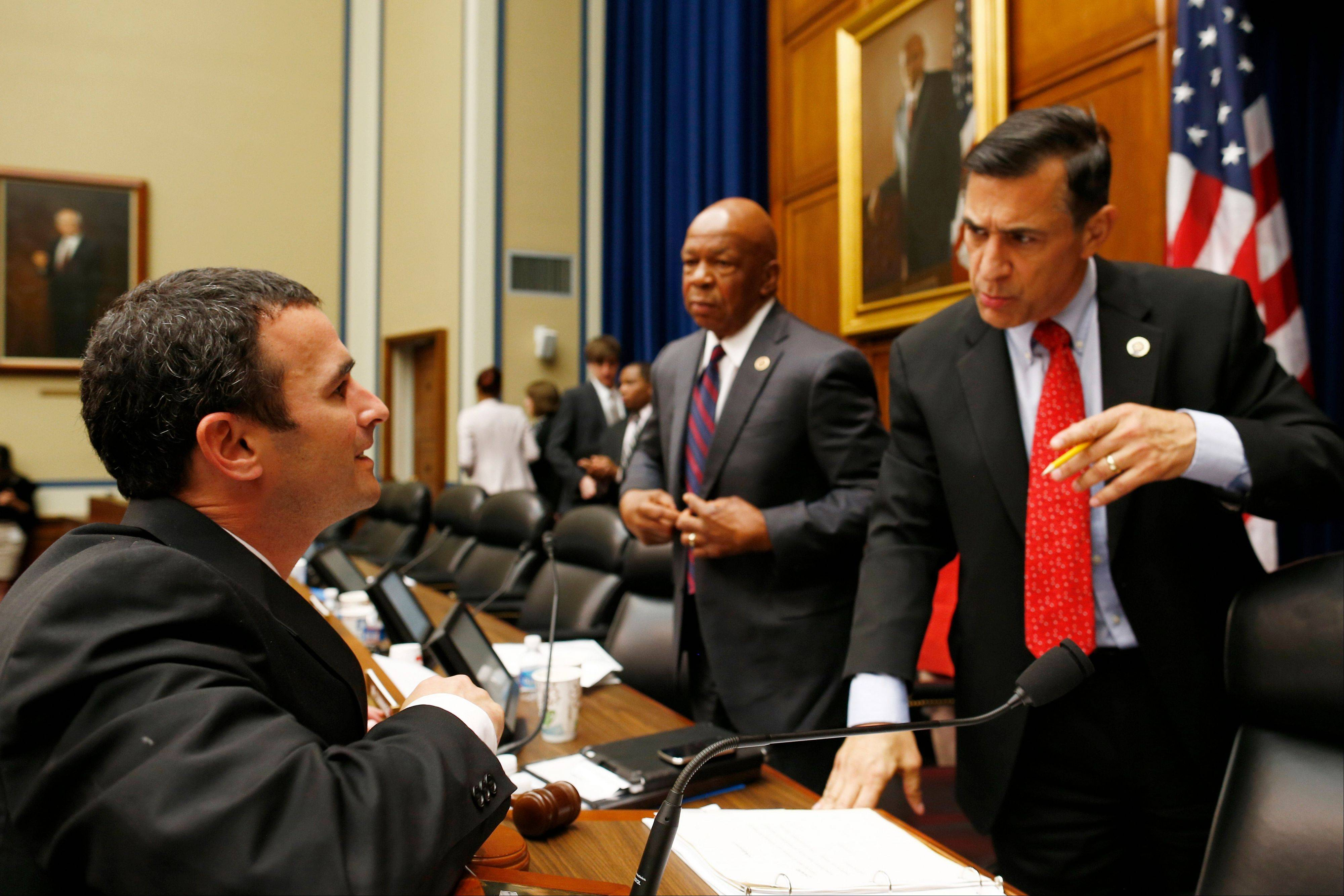 Acting IRS commissioner Danny Werfel, left, talks Thursday with House Oversight and Government Reform Committee Chairman Rep. Darrell Issa, a California Republican, right, accompanied by the committee�s ranking Democrat Rep. Elijah Cummings, a Maryland Democrat, on Capitol Hill in Washington after he testified before the committee�s hearing regarding IRS conference spending.