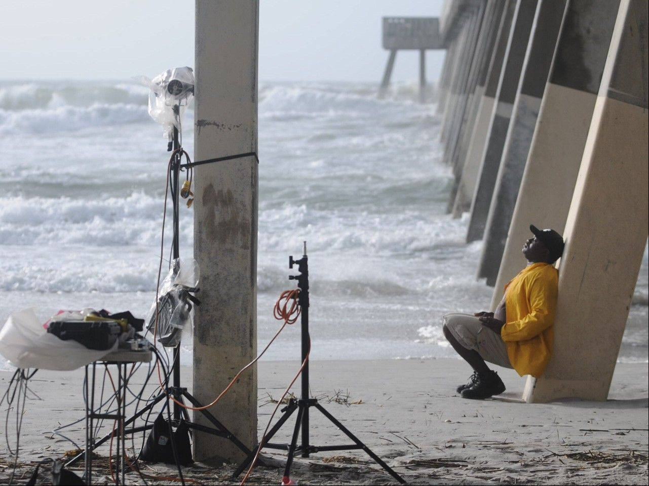 Paul Jackson with CNN�s storm coverage team waits Friday to do a live shot under the Johnnie Mercer�s Pier in Wrightsville Beach, N.C. Tropical Storm Andrea is bringing rain and wind to Carolinas, causing thousands to lose power and streams to swell. The storm was racing through South Carolina early Friday and was expected to move into eastern North Carolina by midday.