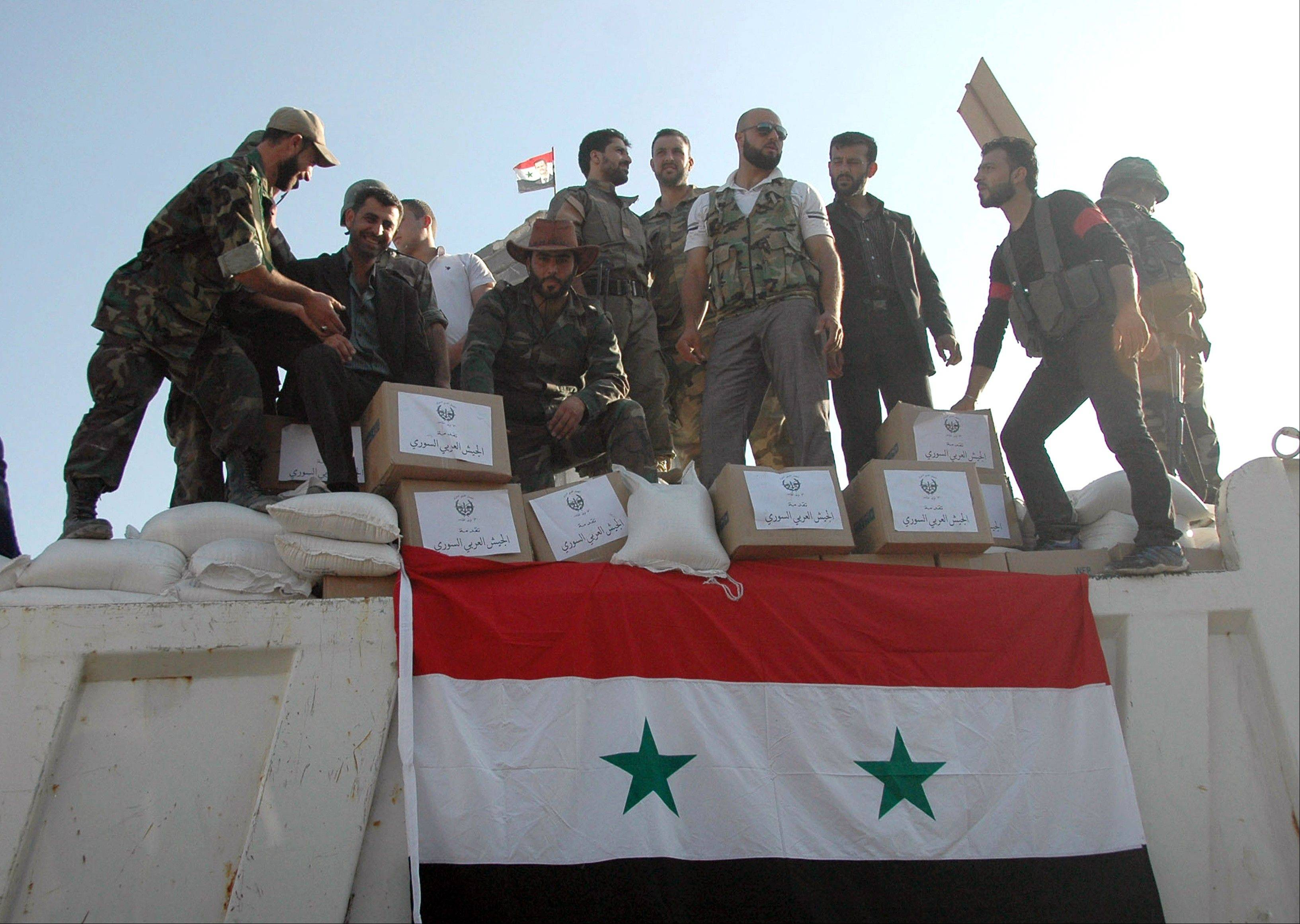 In this photo released Wednesday by the Syrian official news agency SANA, Syrian soldiers loyal to President Bashar Assad stand on a truck full of aid supplies, in Qusair, Syria. Syrian troops and their Lebanese Hezbollah allies captured a strategic border town Wednesday after a grueling three-week battle, dealing a severe blow to rebels and opening the door for President Bashar Assad�s regime to seize back the country�s central heartland. The regime triumph in Qusair, which Assad�s forces had bombarded for months without success, demonstrates the potentially game-changing role of Hezbollah in Syria�s civil war.