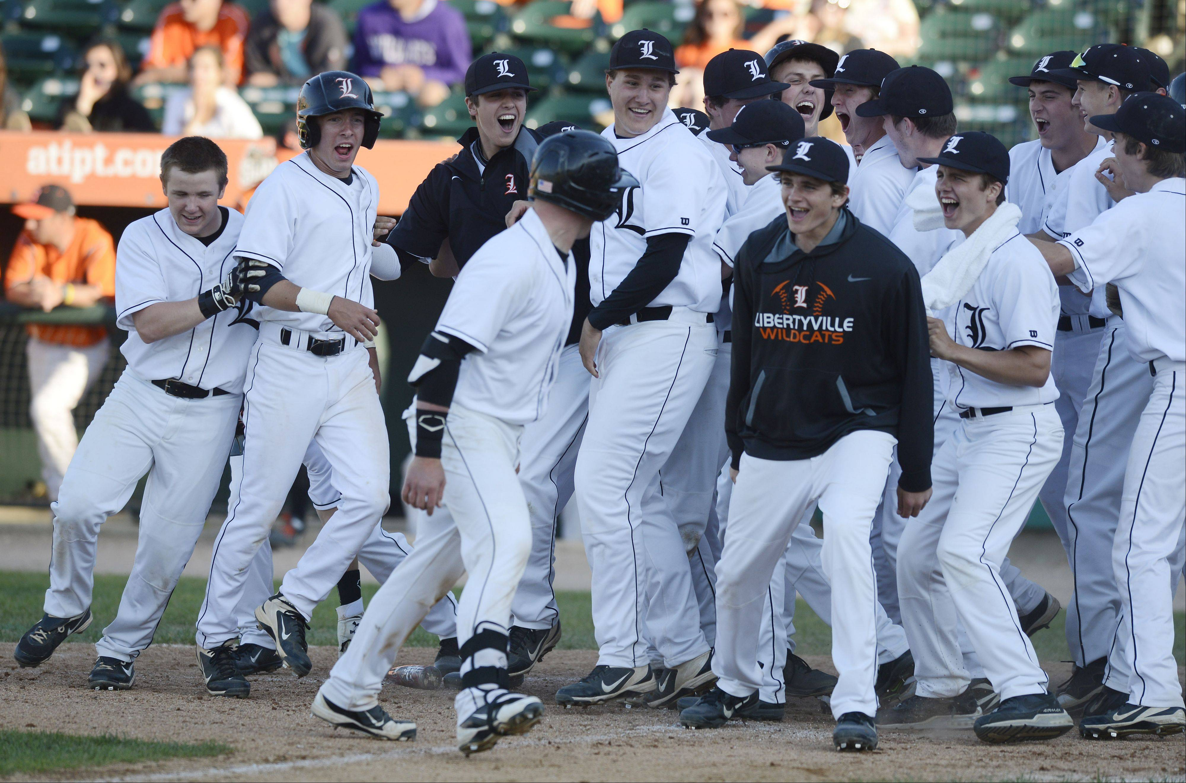Libertyville�s Evan Skoug is greeted at the plate by his teammates after hitting a fourth-inning grand slam against St. Charles East during the Class 4A state baseball semifinals at Silver Cross Field in Joliet Friday.